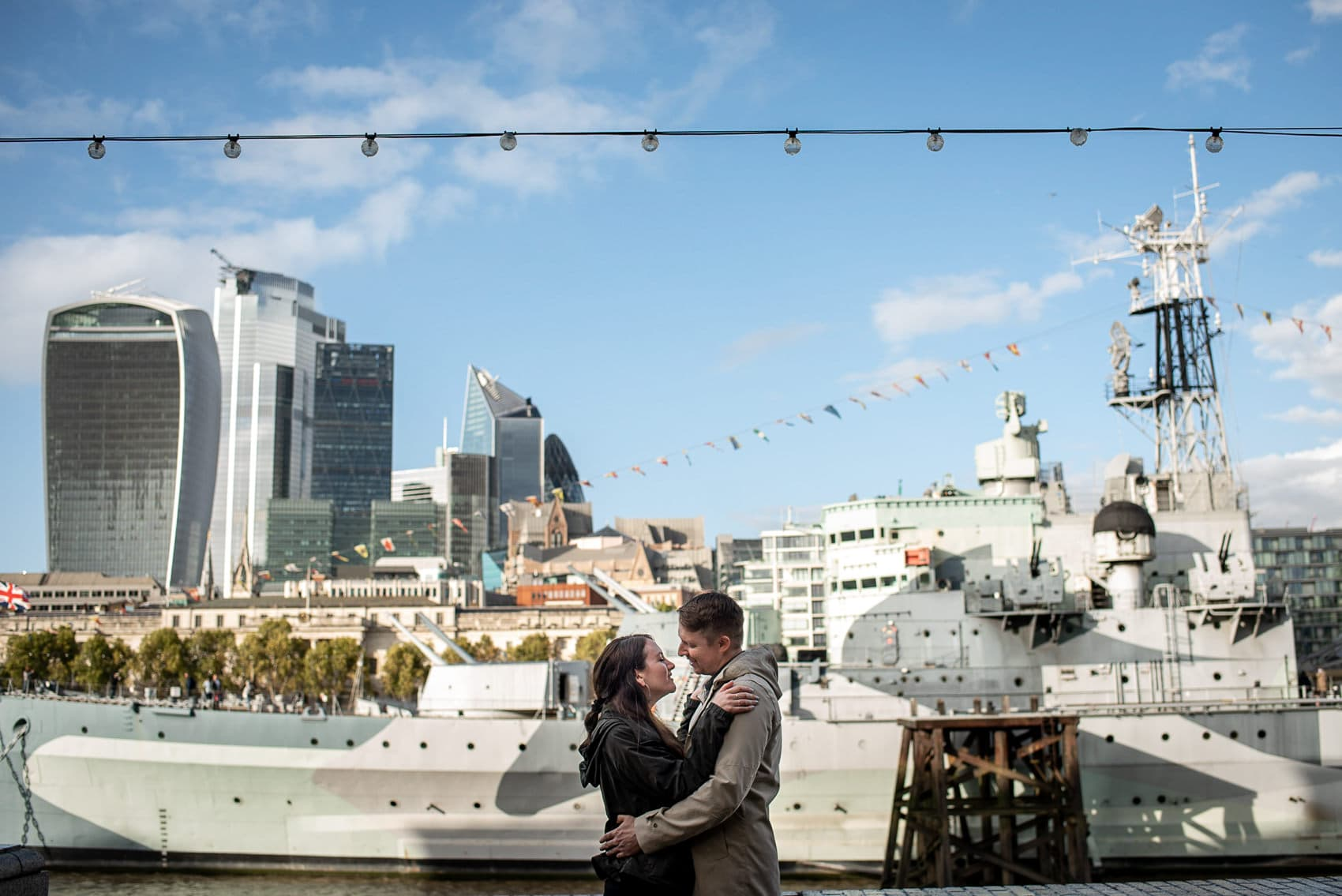 Photo of couple hugging on their photo shoot with the HMS Belfast and London City in the background