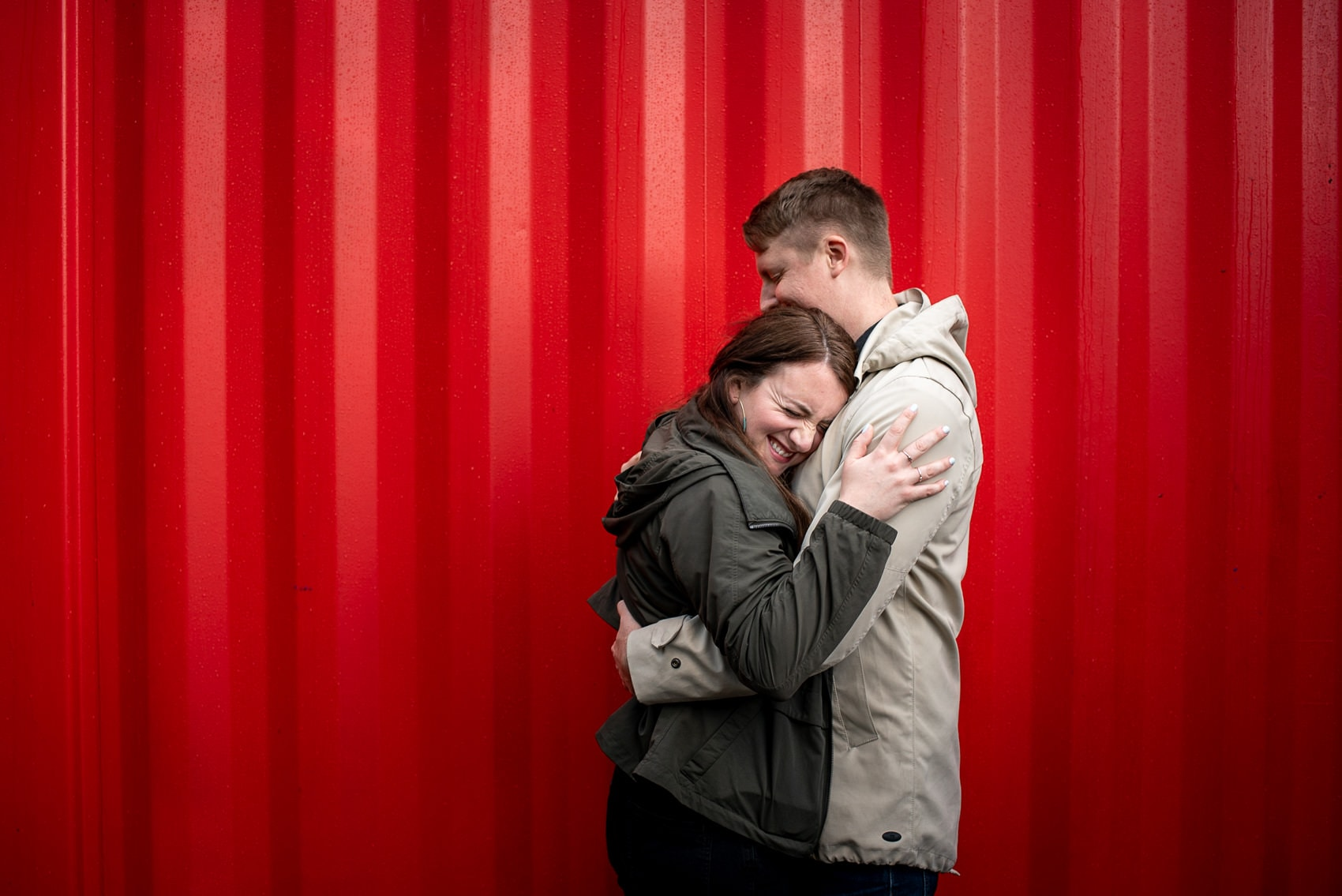 Photo of couple hugging in front of red container taken by London engagement photographer Matt Badenoch