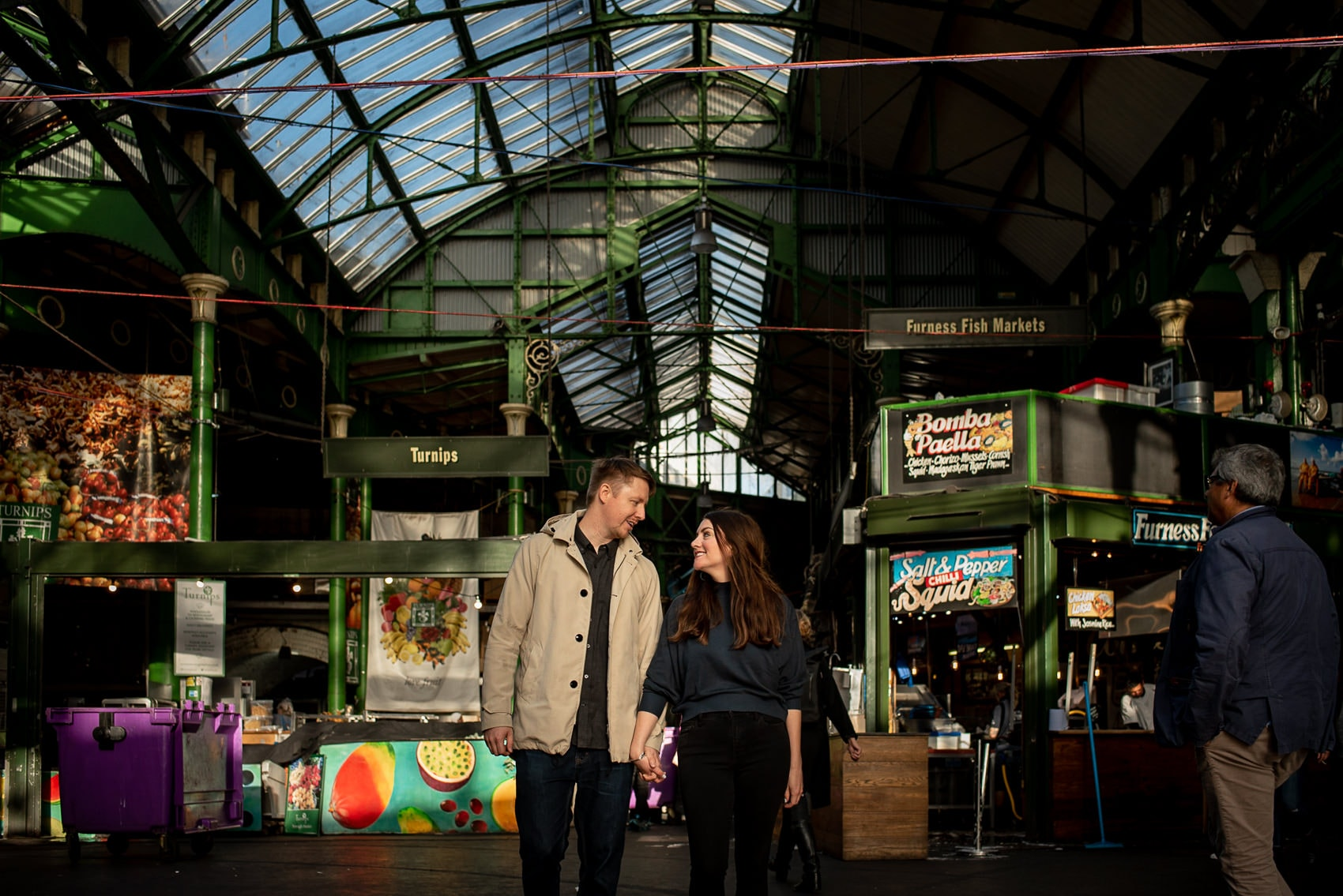 Photo of couple walking through Borough Market during their London engagement photo shoot