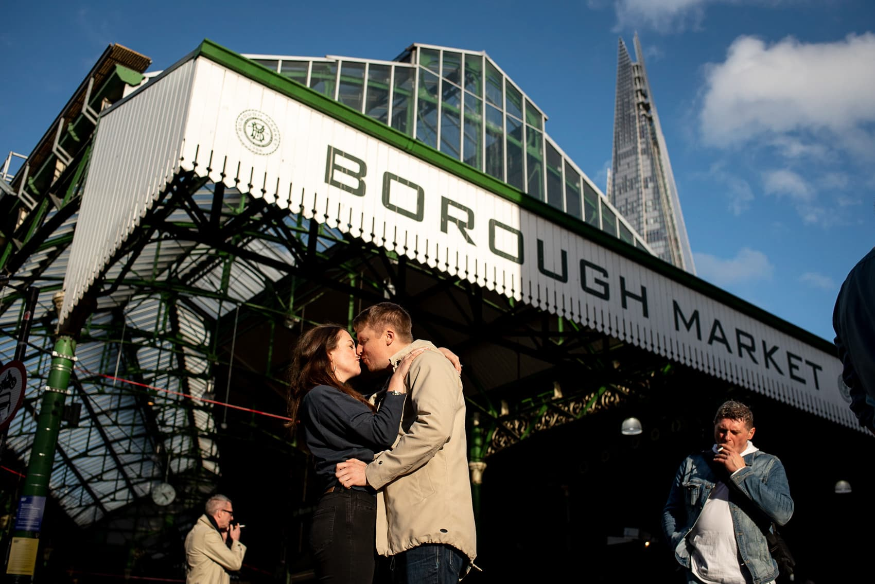 Street photography photo of couple kissing in front of Borough Market sign and the Shard with blue sky