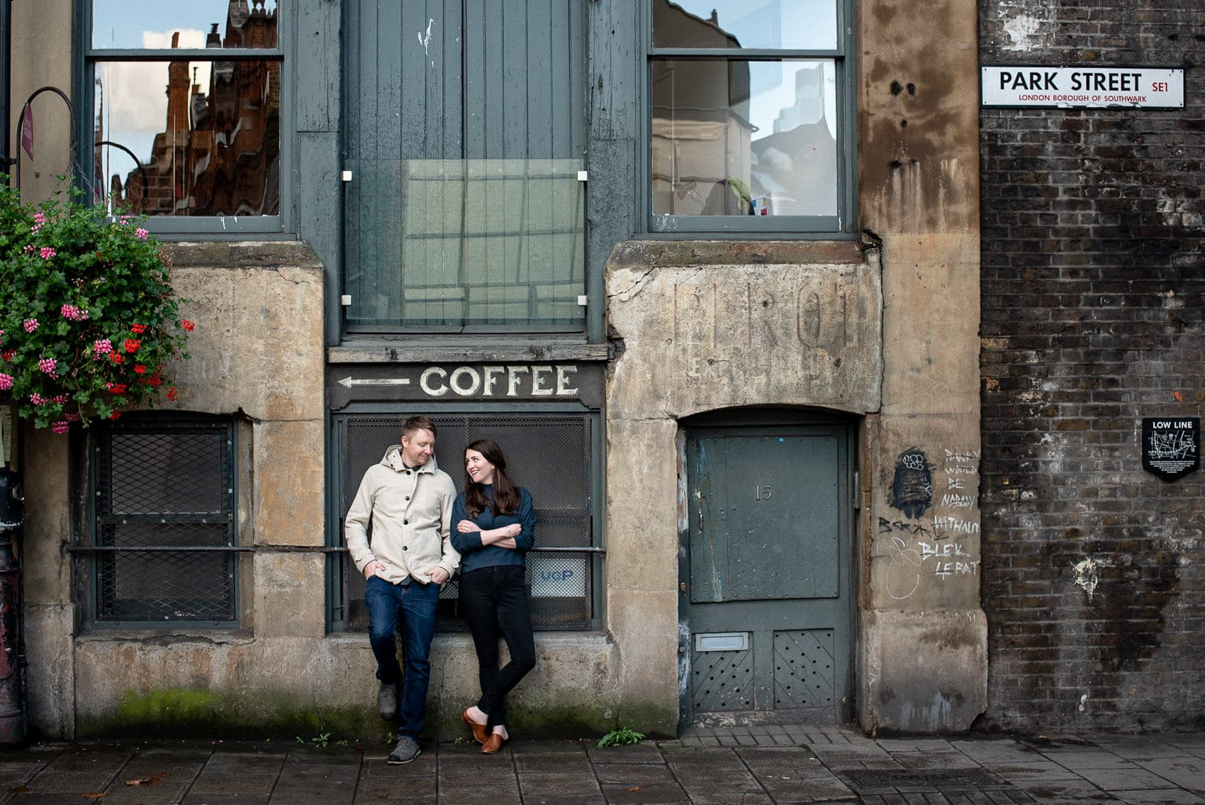 Photo of couple posing on Park Street in front of scene from movie Lock Stock and Two Smoking Barrels
