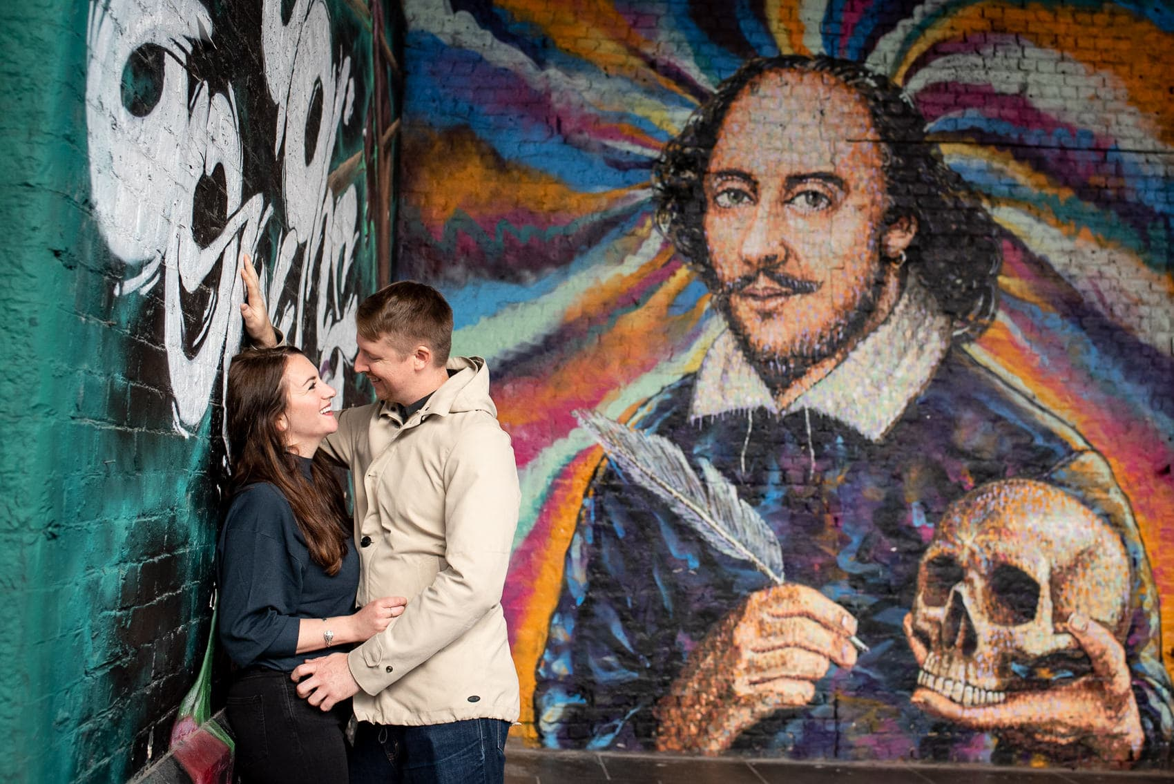 couple smiling in front of Shakespeare graffiti near borough market in london