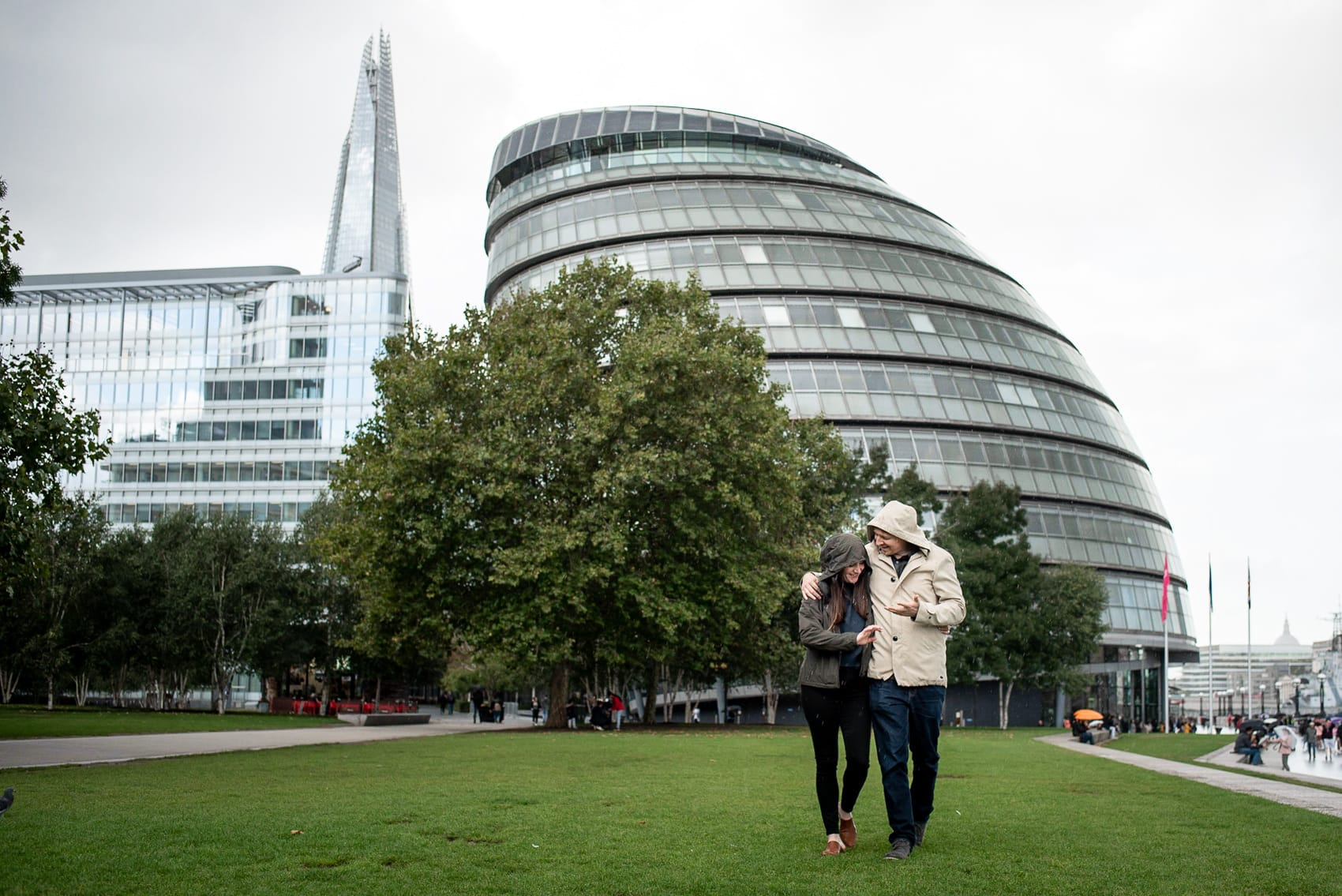 Photo of couple walking on the grass in front of City hall on a wet London day