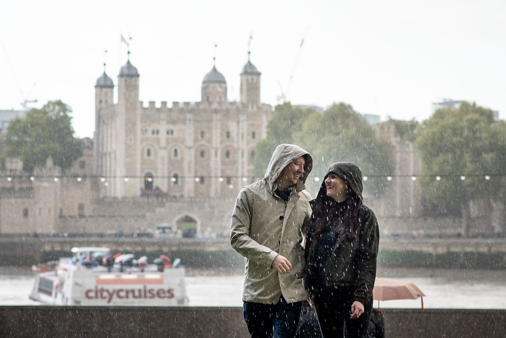 Couple laughing in heavy rain during their London engagement shoot with the Tower of London in the background