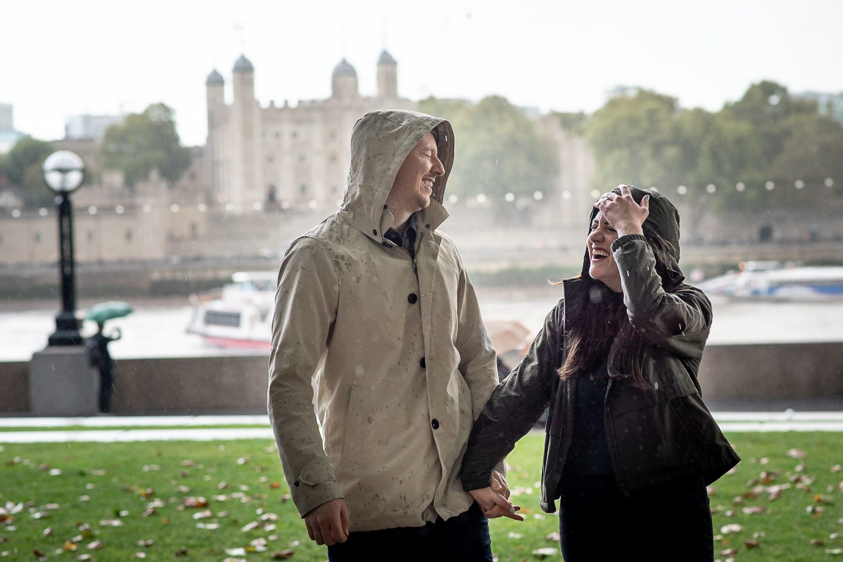 Couple laughing in the rain with the Tower of London in the background during their engagement shoot