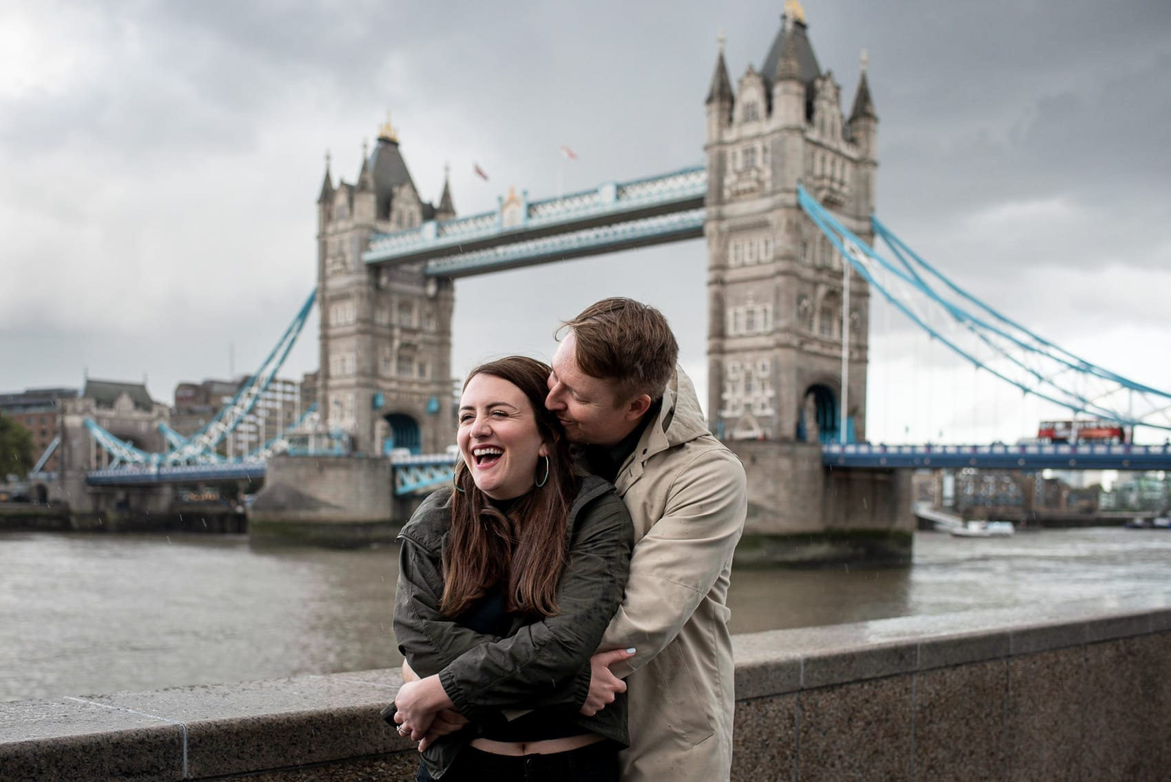 Photo of couple laughing and hugging next to the Tower of London on a wet and cloudy day