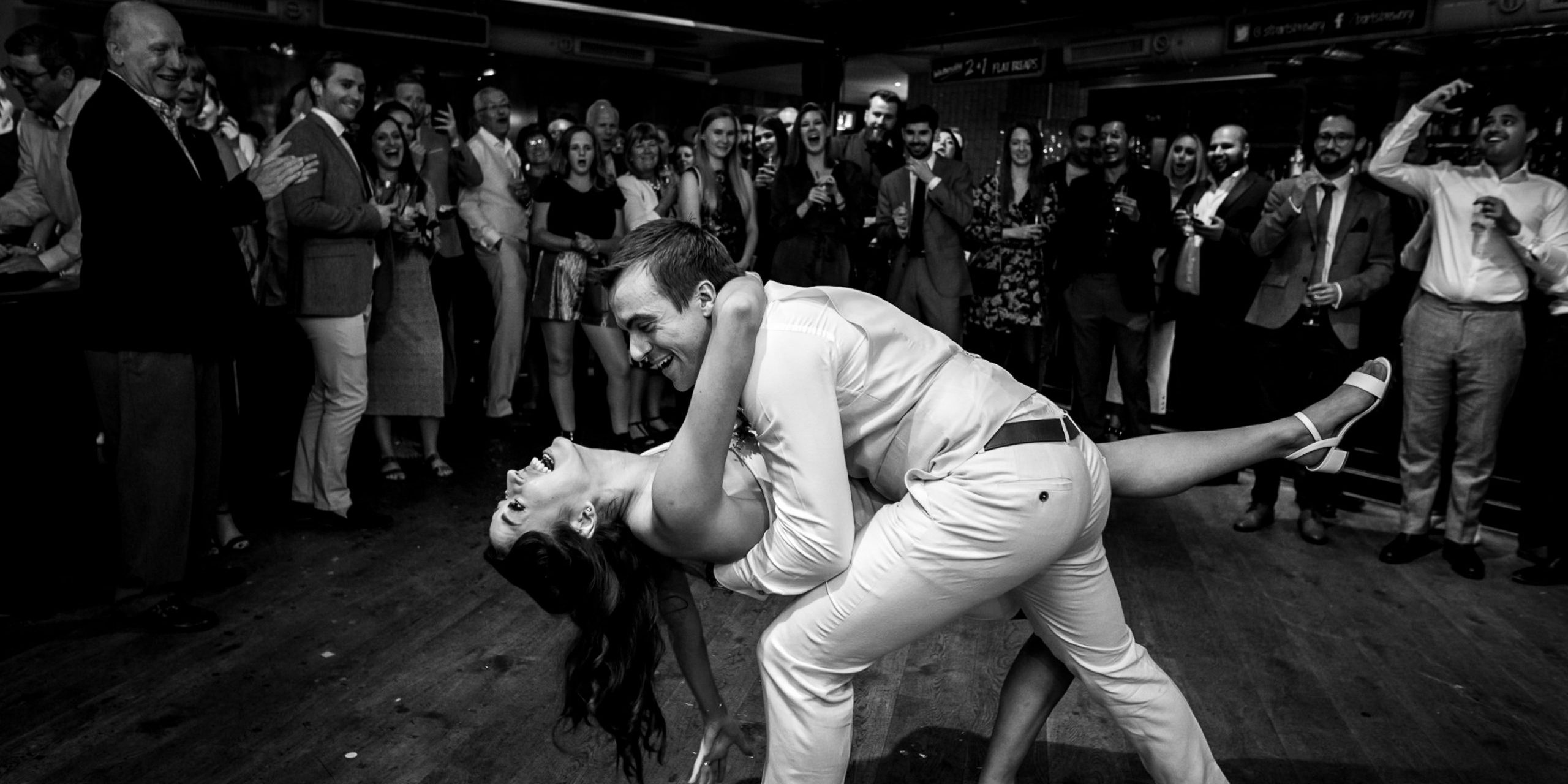 Photo of bride and groom doing their first dance at their St Barts Brewery wedding in London while their guests cheer them on