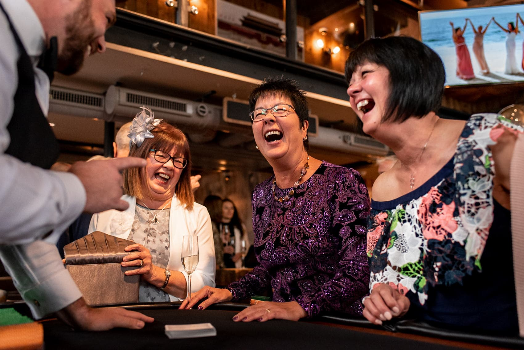 Weddings guests laughing with a magician after his trick at a St Barts Brewery wedding