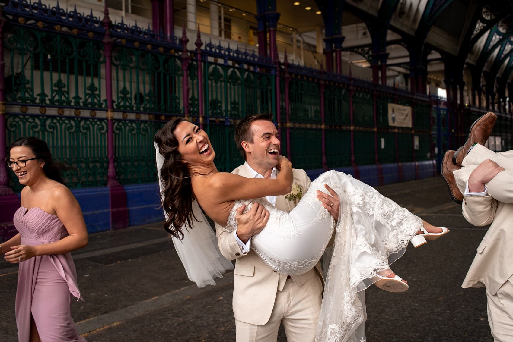Groom lifting up his bride and laughing in Smithfields Market
