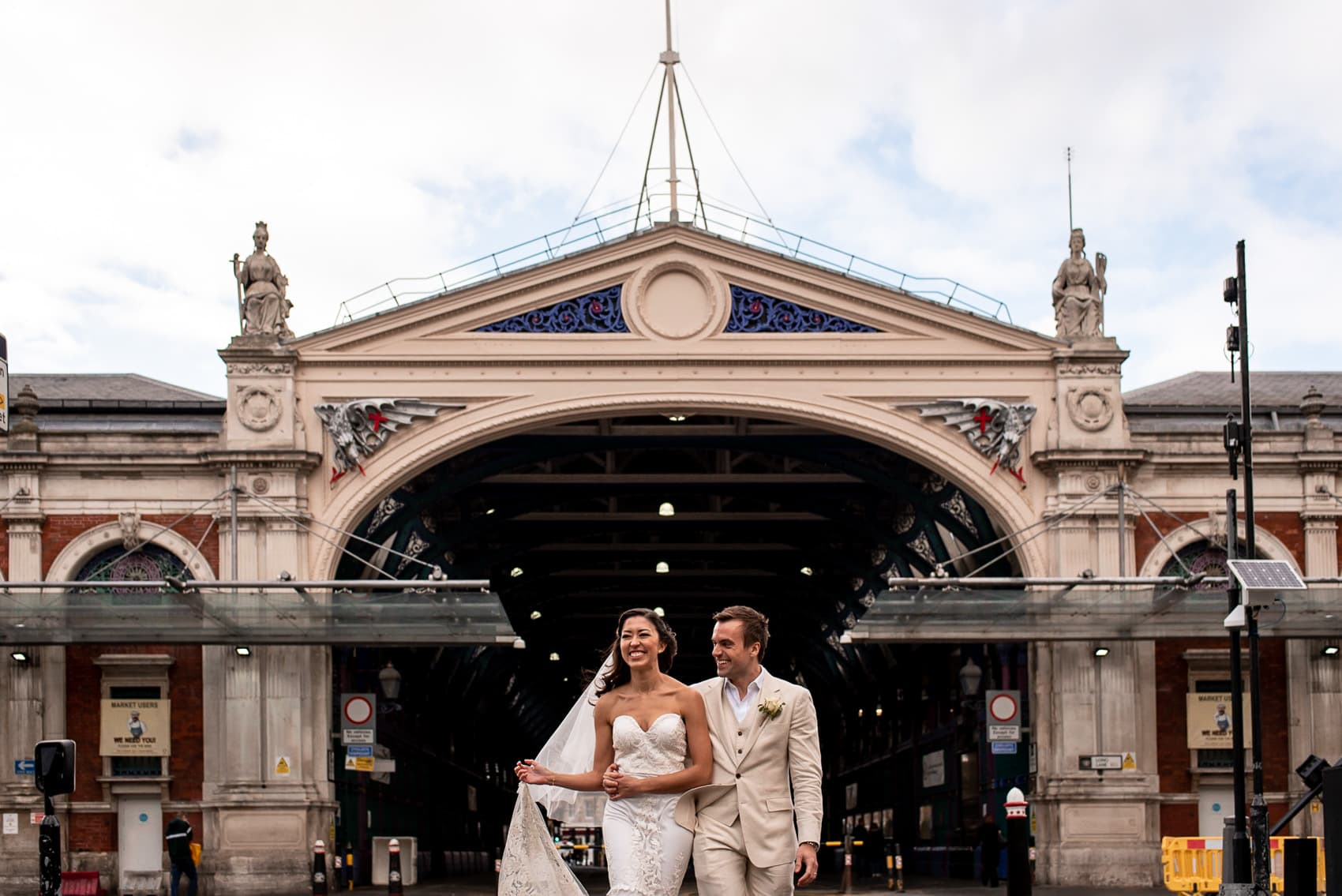 Bridal portrait of bride and groom walking outside of Smithfields Market at their St Barts Brewery wedding