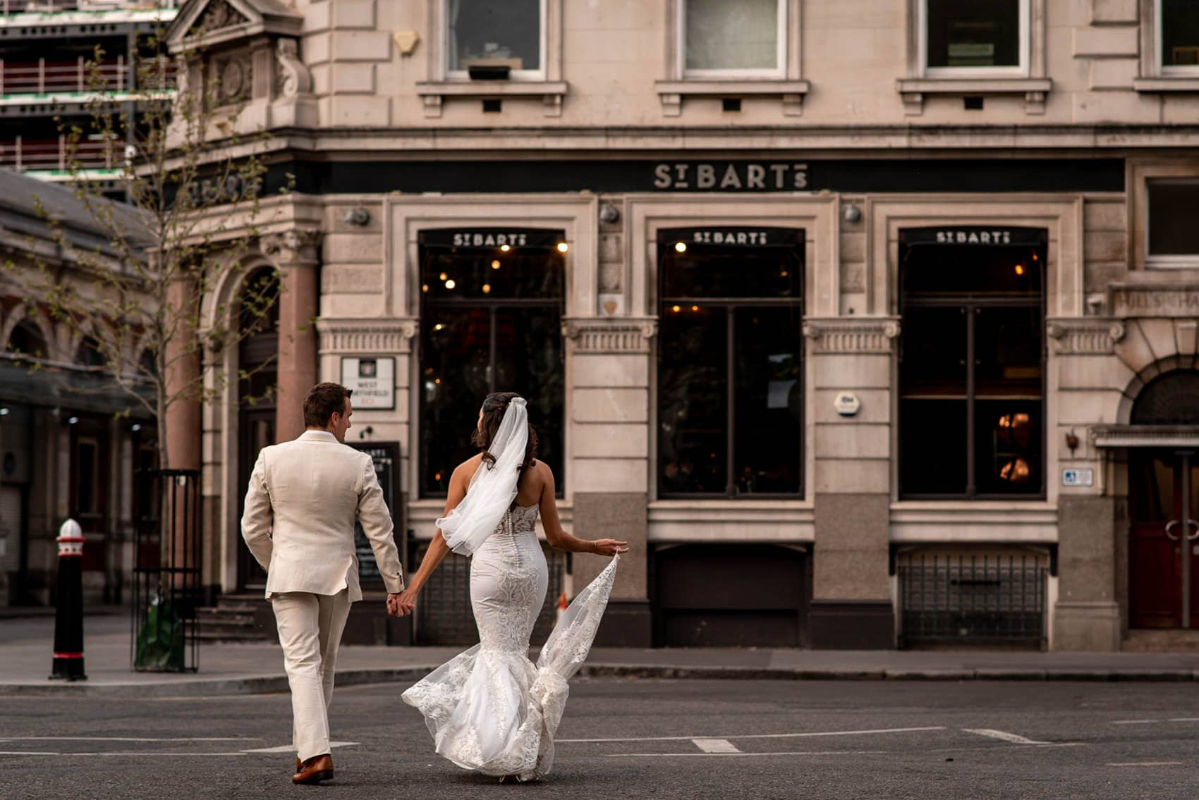 bride and groom in their wedding dresses walking towards St Barts Brewery