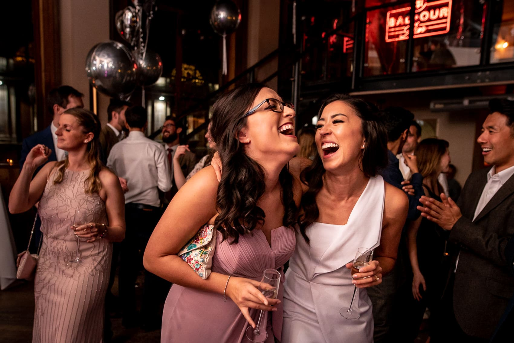 Bride and maid of honour laughing on the dance floor at a St Barts Brewery wedding
