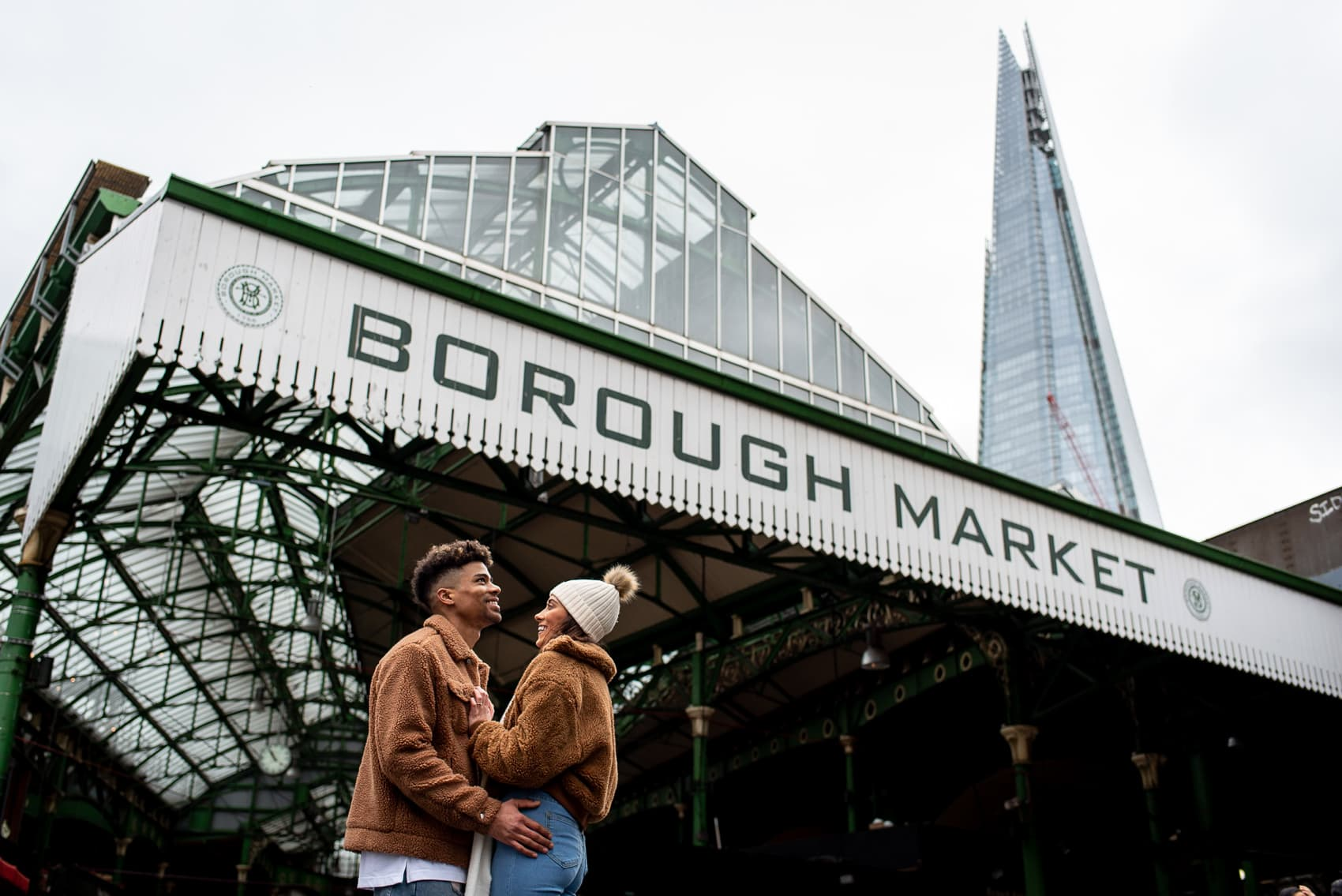 Recently engaged couple posing in front of Borough Market and the Shard on their London proposal shoot