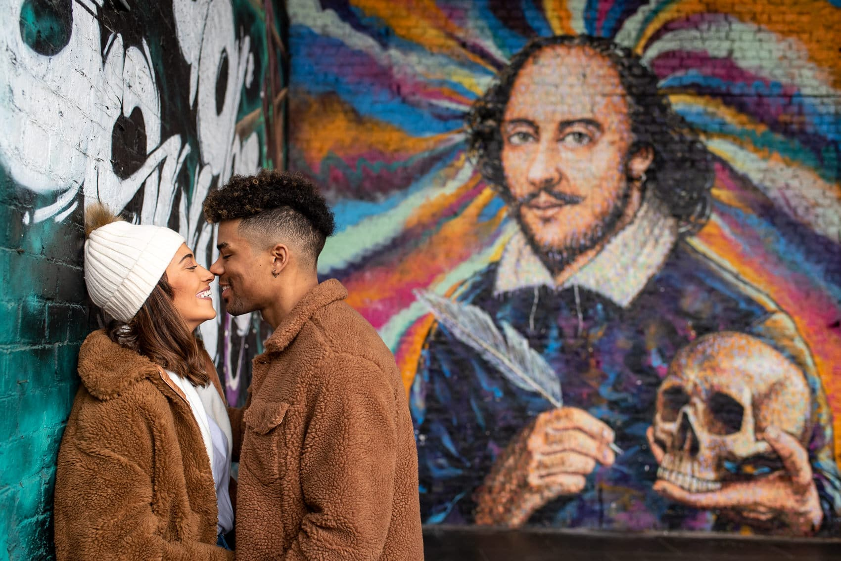 Photo of a recently engaged couple smiling in front of the colourful Shakespeare Graffiti next to Borough Market