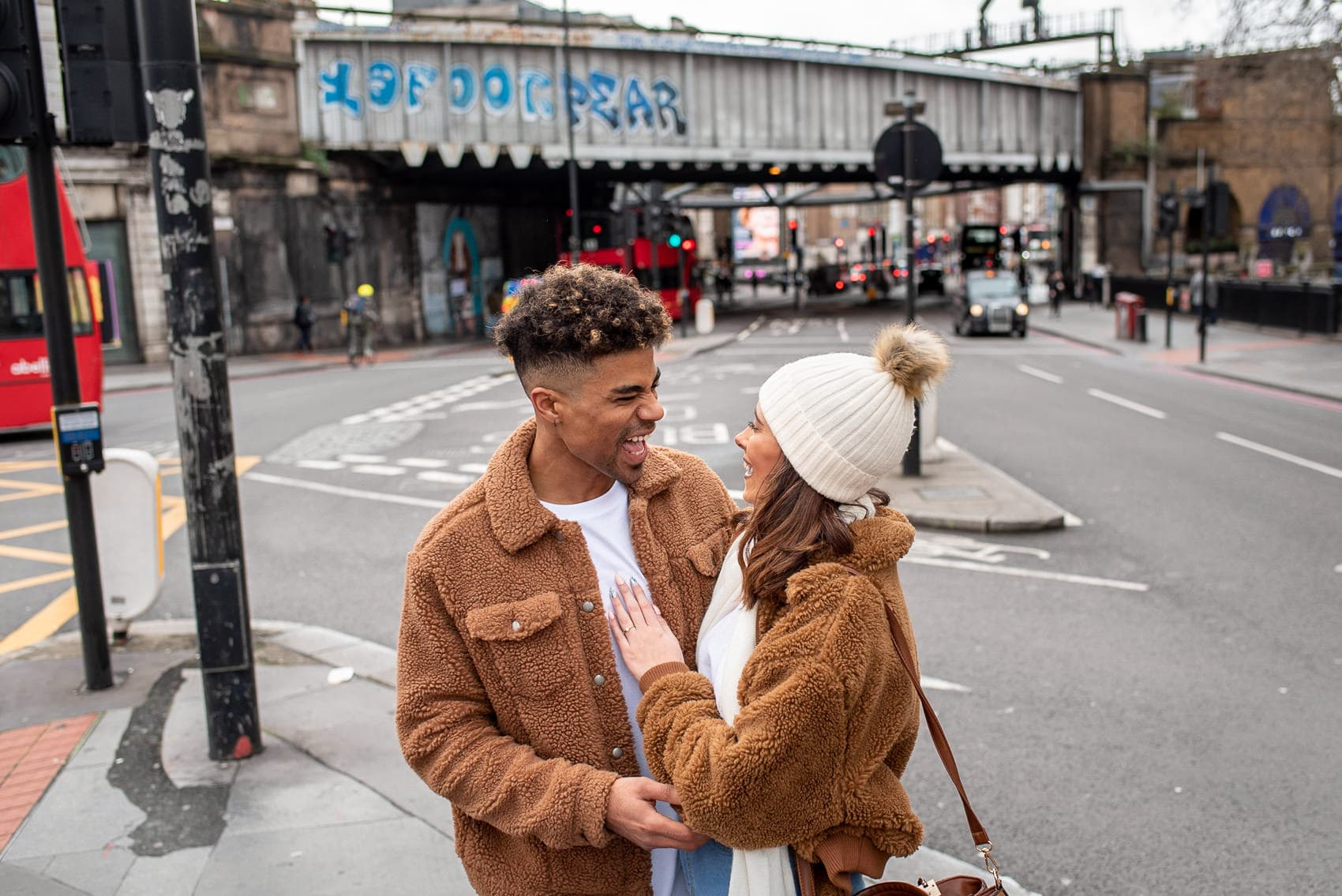 Couple laughing on their London engagement shoot
