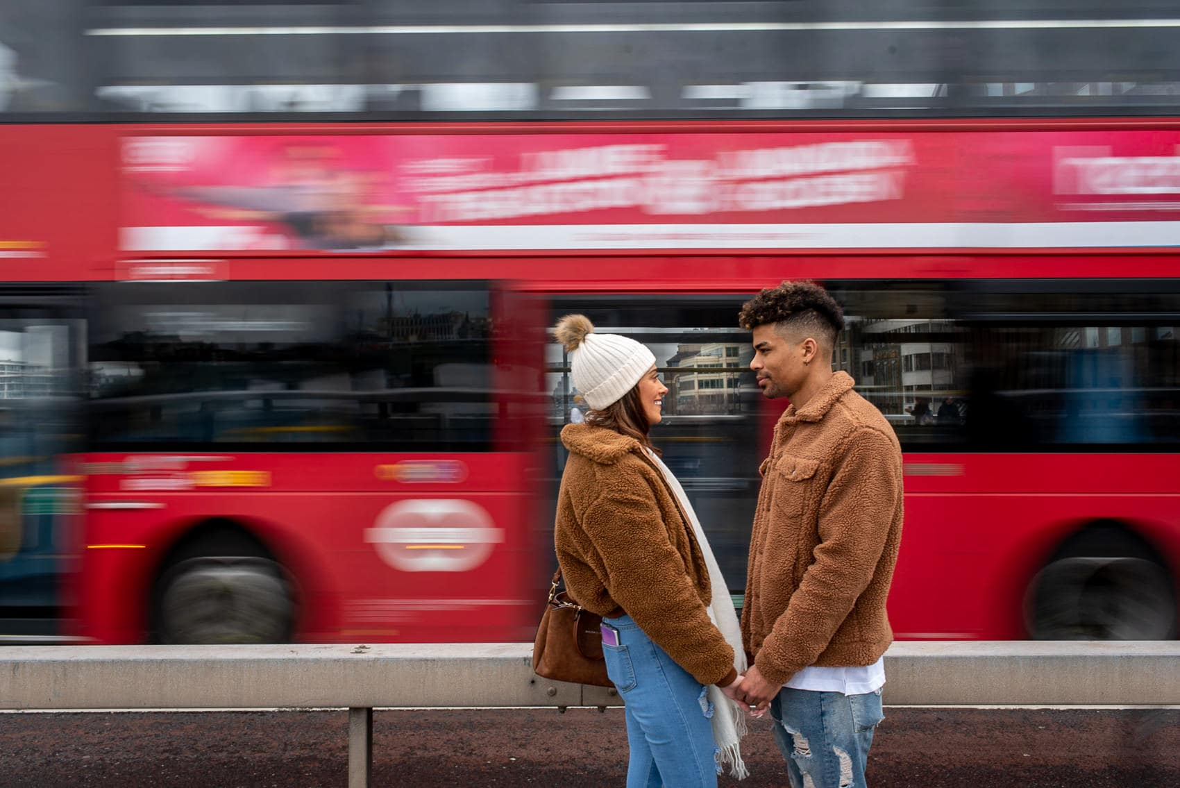Couple posing in front of red London bus as it speeds past. Taken using motion blur