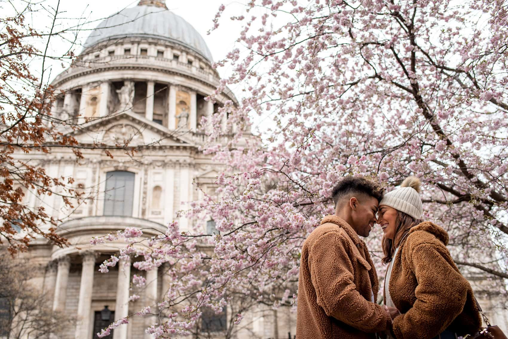Photo of couple in front of St Pauls Cathedral with Cherry Blossoms in March during their engagement shoot