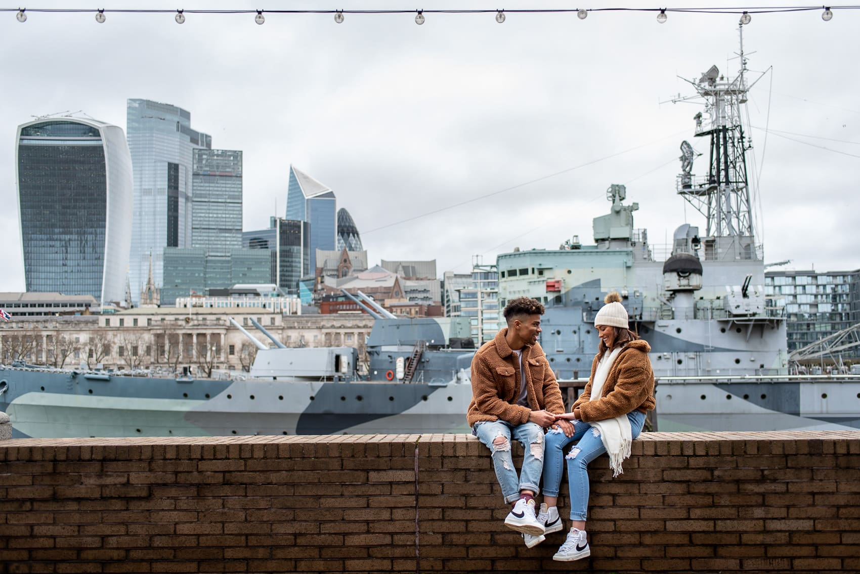 Couple sitting next to HMS Belfast and the city of London on their wedding proposal shoot
