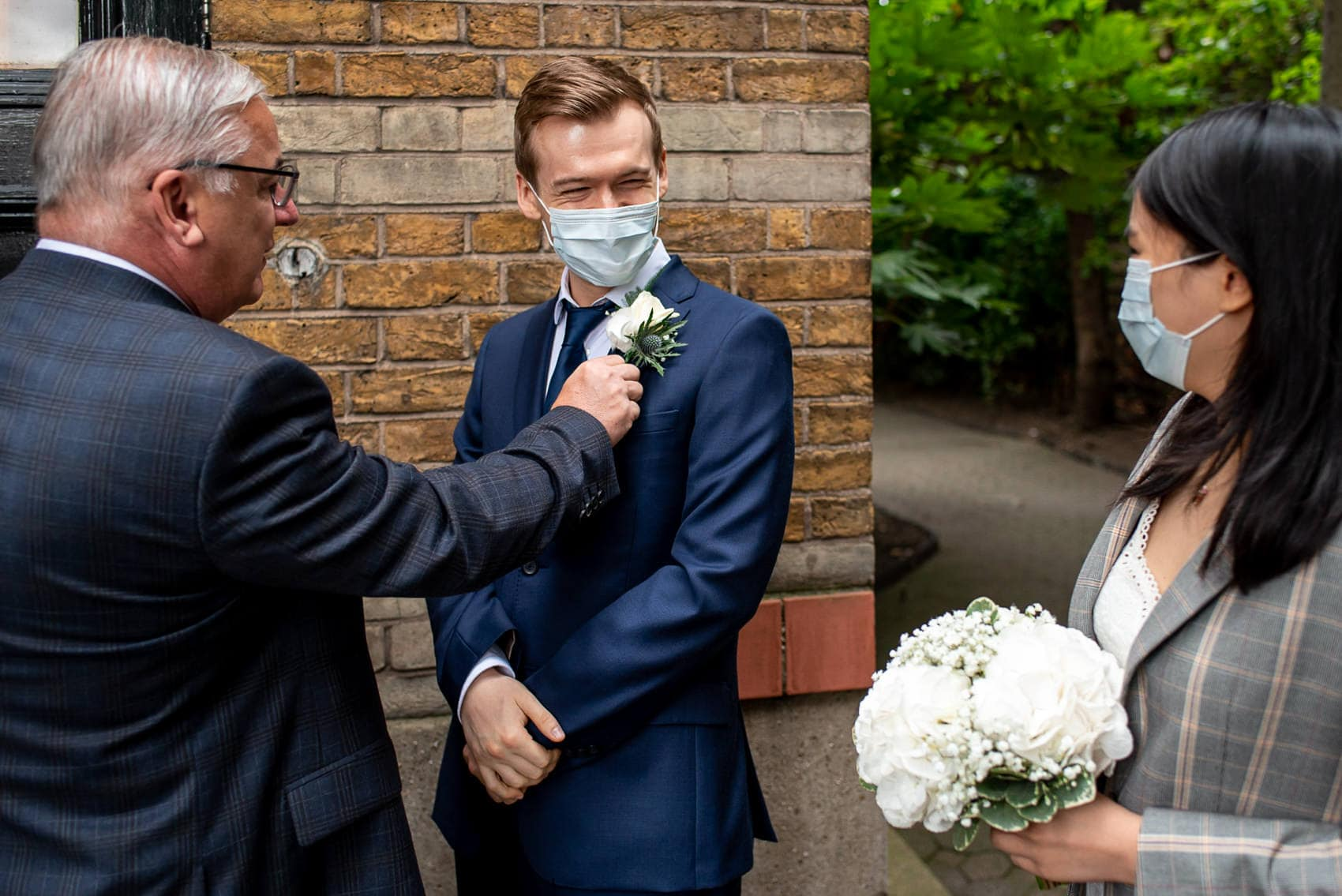 Photo of dad fixing his son's Boutonniere while wearing a mask for his wedding during Coronavirus pandemic