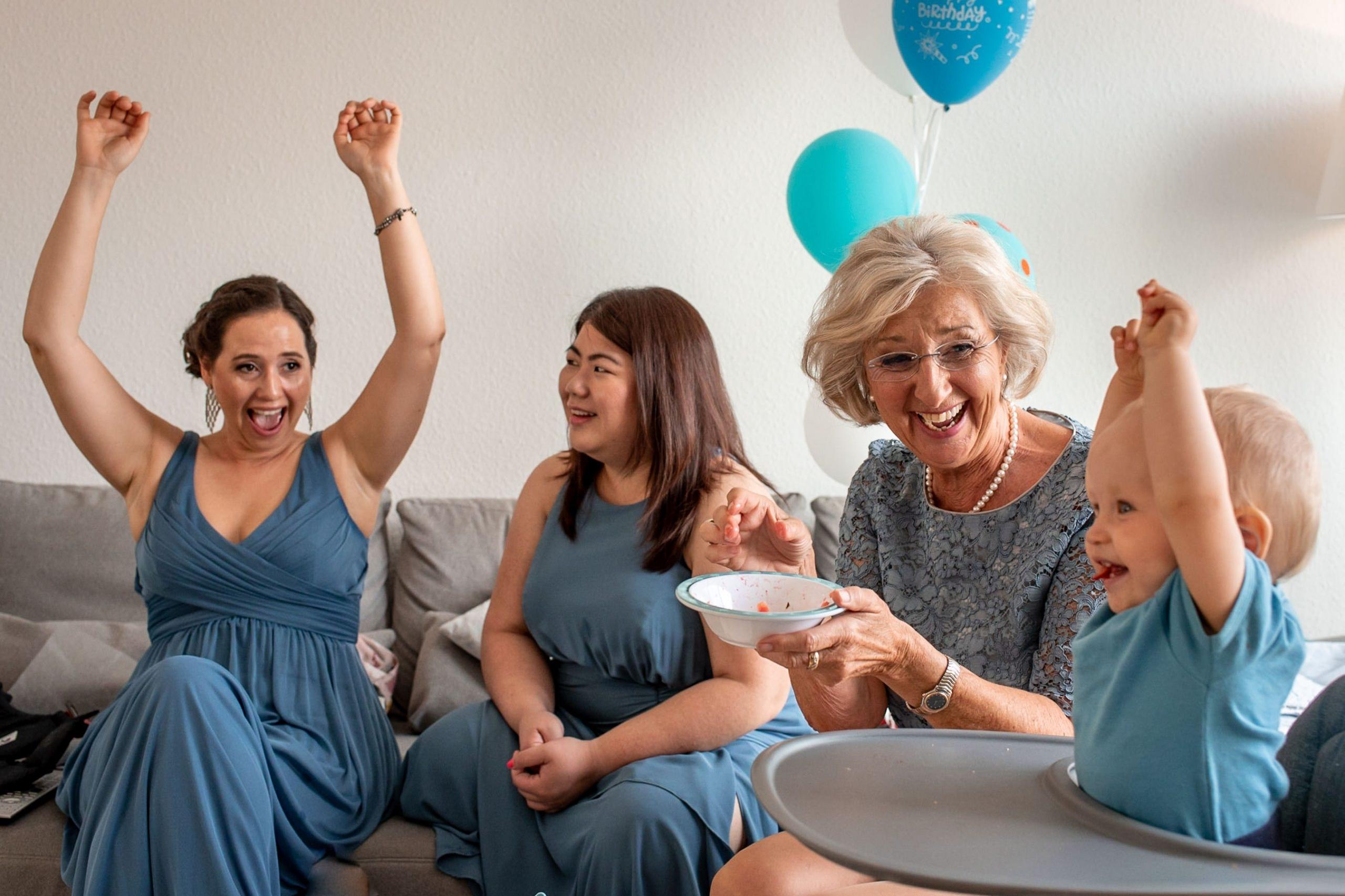 bridesmaids in blue dresses celebrating during bridal prep during the bride's baby at her Düsseldorf Destination wedding