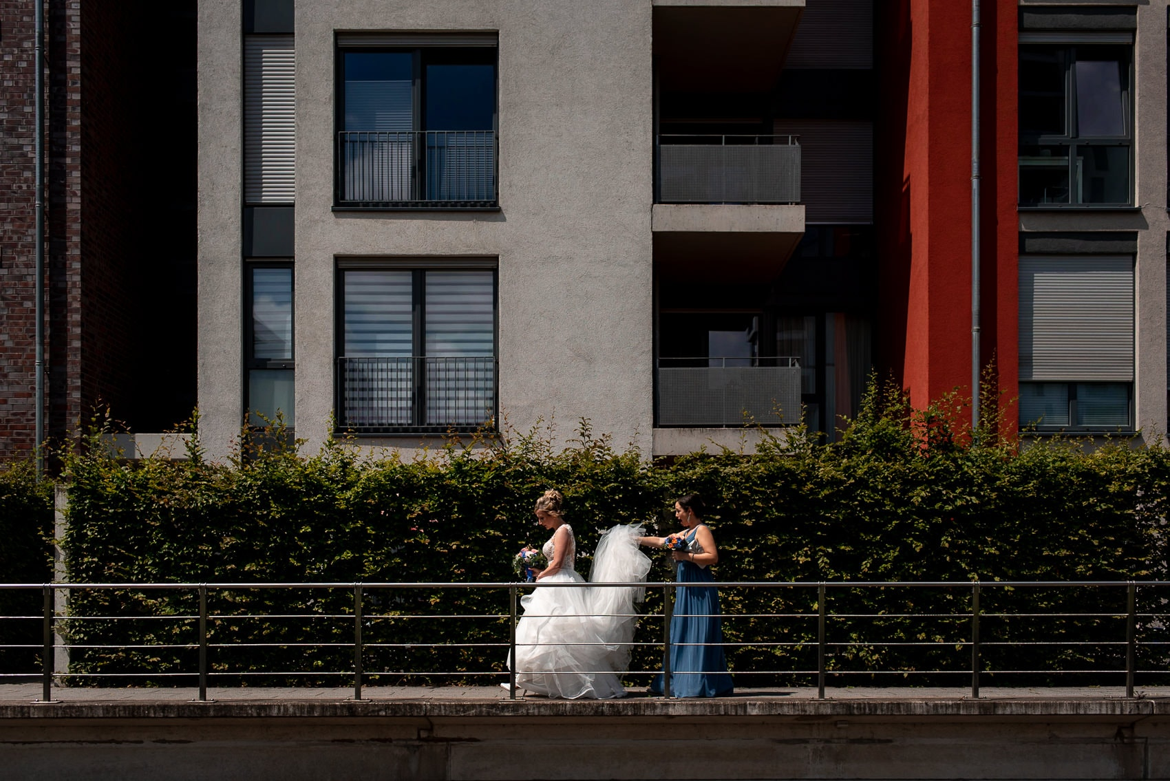 Bride in her wedding dress walking with her bridesmaid in an urban location