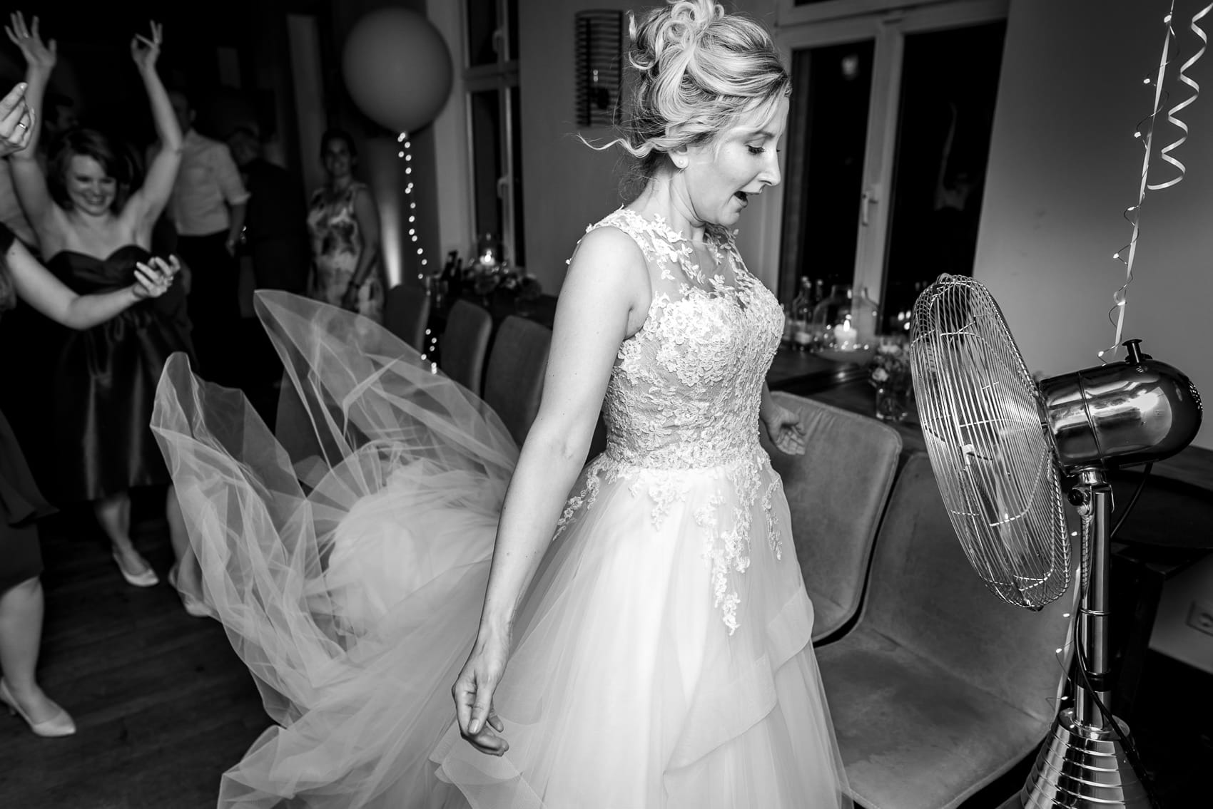 Photo of bride cooling herself off with a fan during her wedding dancing party