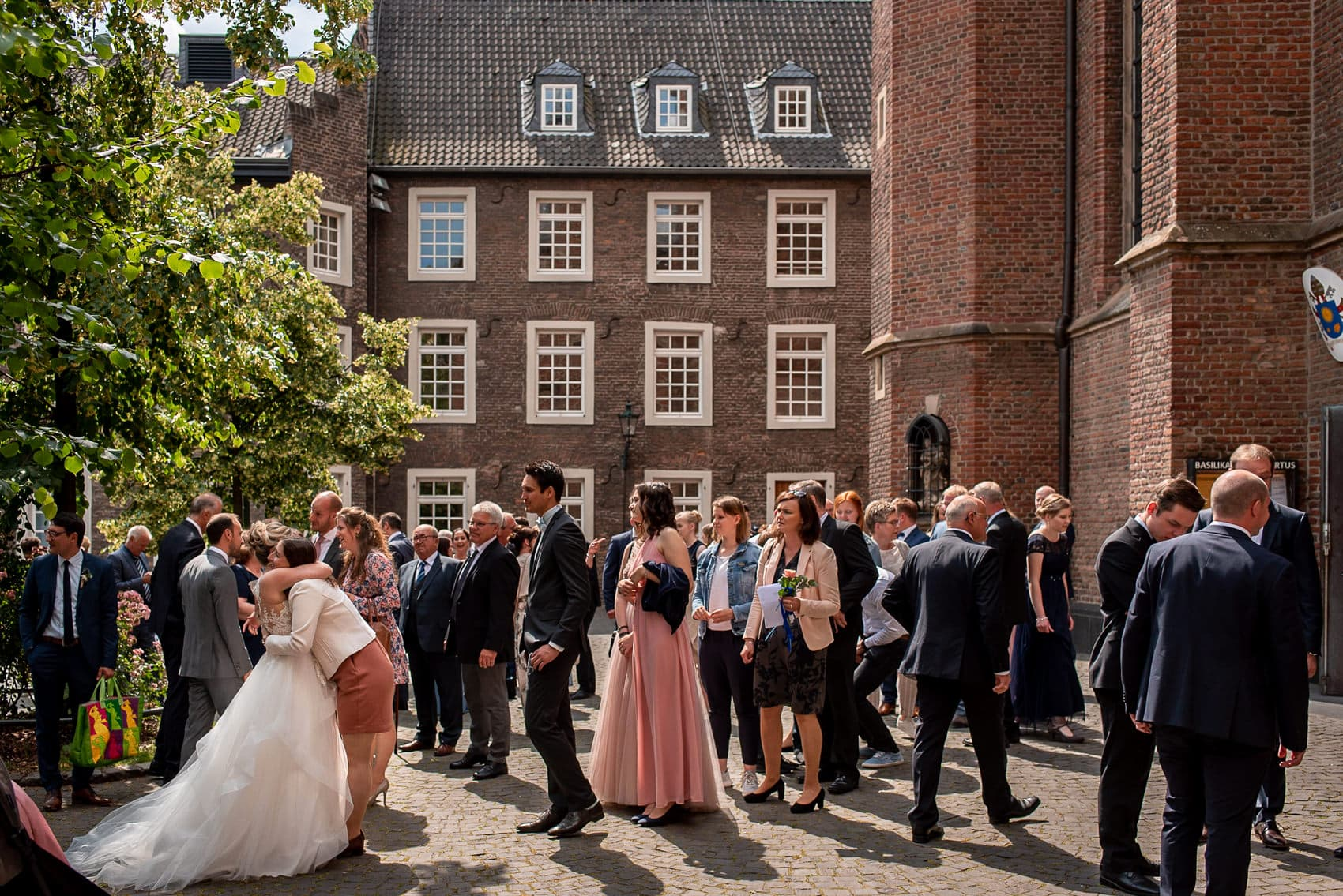 Bride hugging her guests outside the church at her Dusseldorf destination wedding