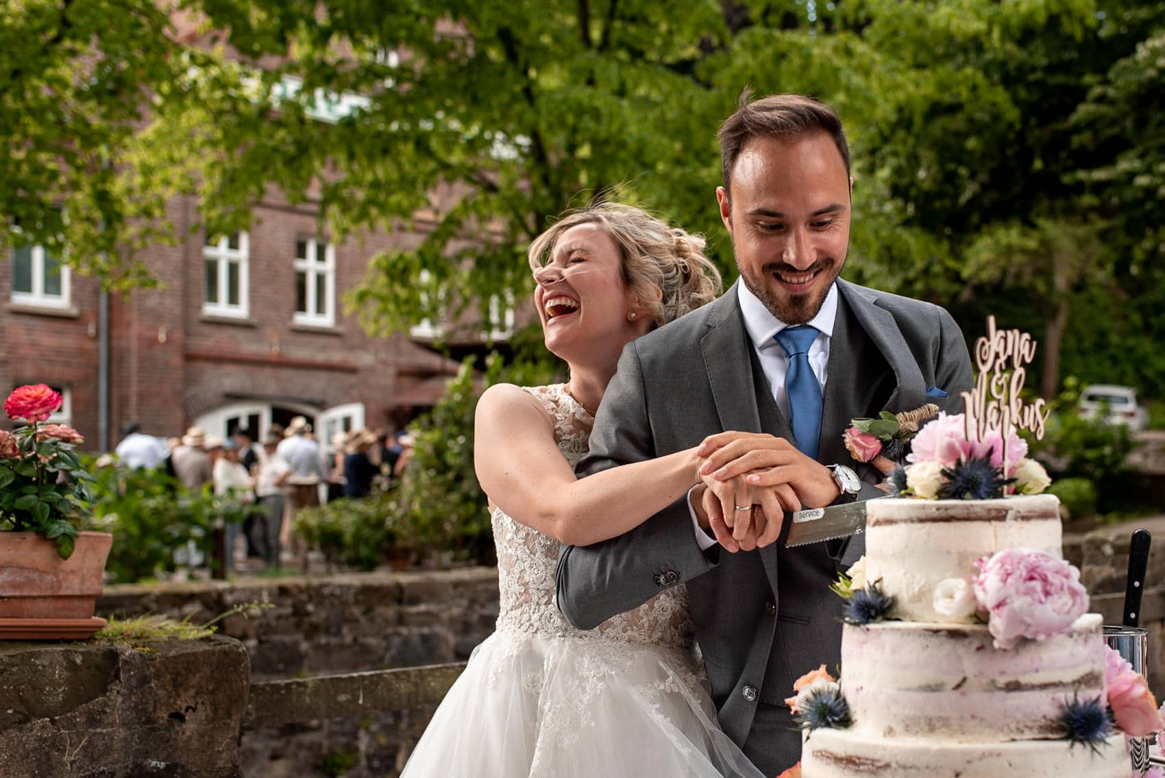 Photo of bride and groom cutting their cake and laughing at the Dusseldorf Destination wedding