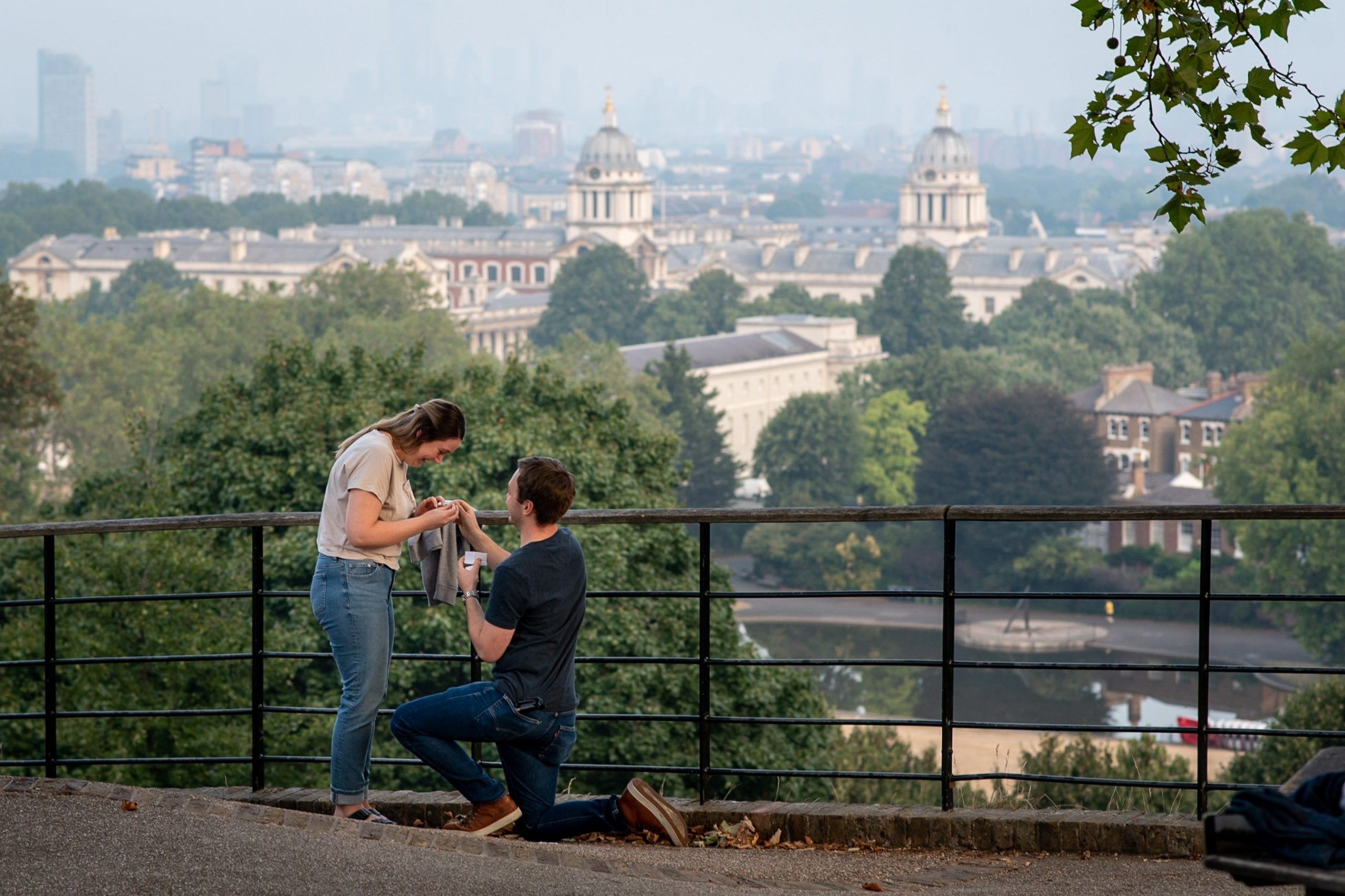 man proposing to his girlfriend at the top of One Tree Hill Vista Point in Greenwich Park with views of London in the background
