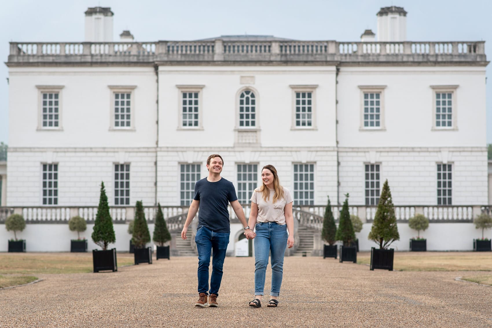 couple walking in front of the Maritime Museum on their Greenwich engagement shoot