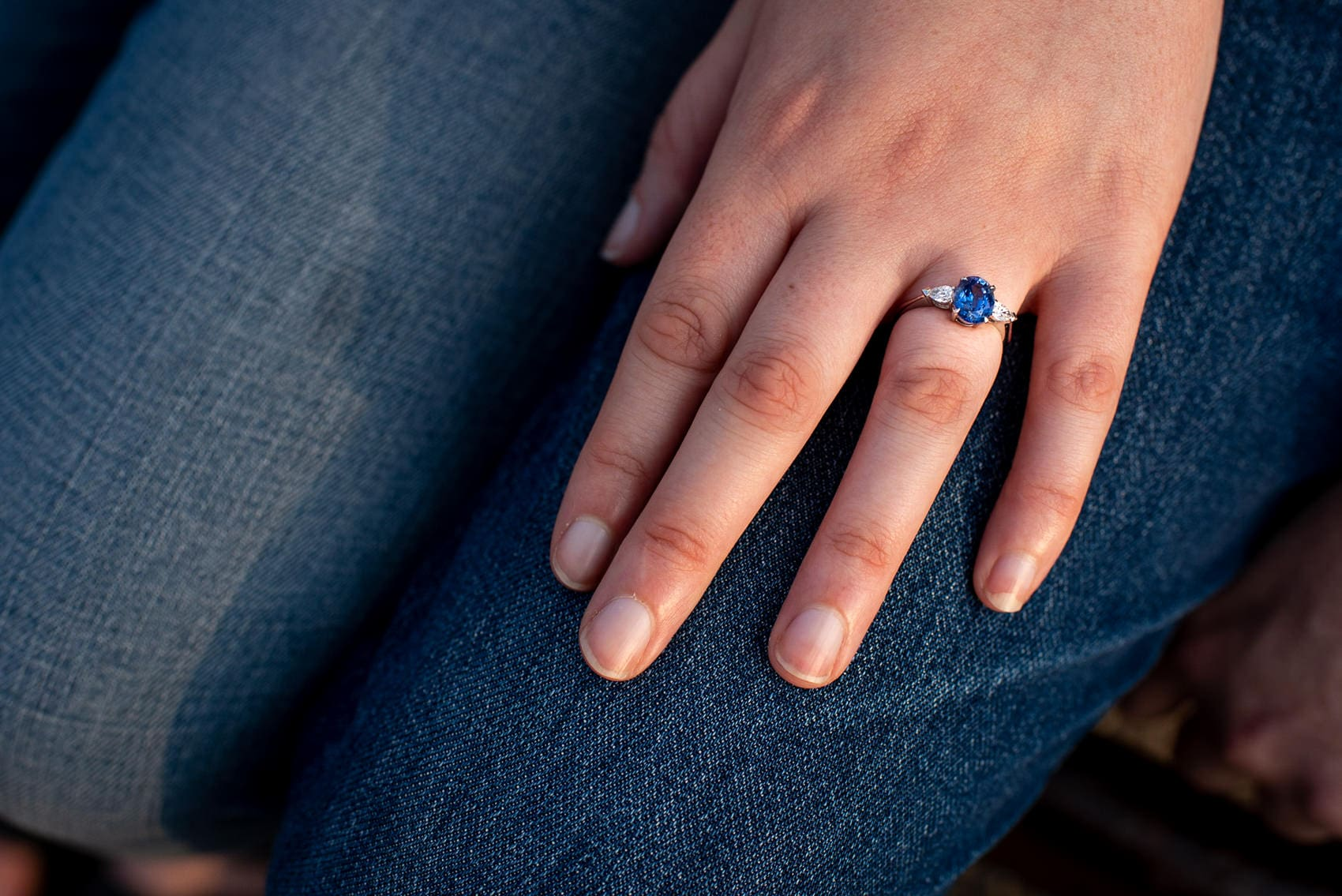 Blue engagement ring with silver wings on hand
