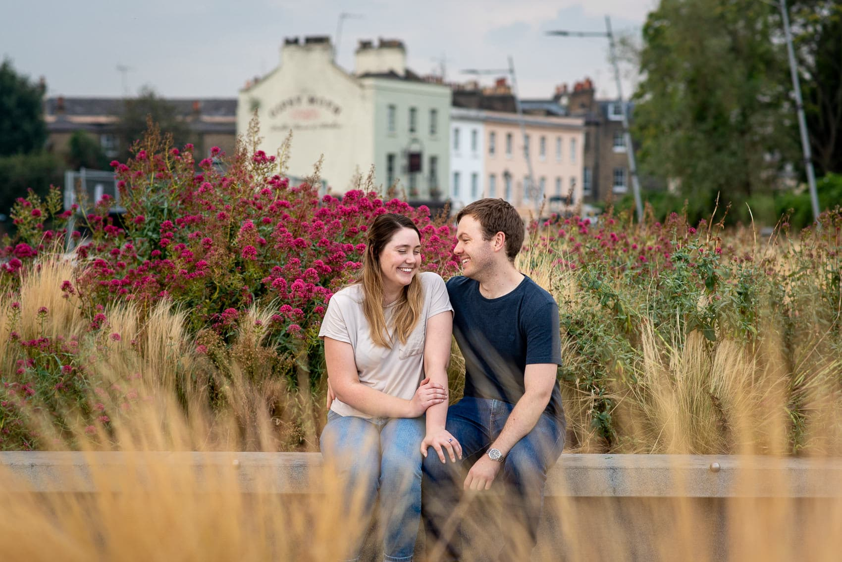 Couple sitting next to flowers in Greenwich and laughing
