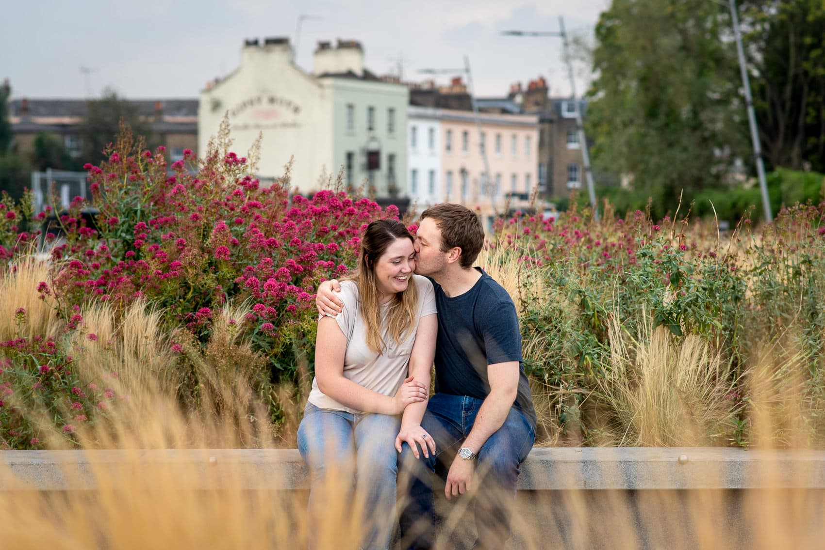 Couple sitting next to flowers in Greenwich and laughing on their proposal photo shoot