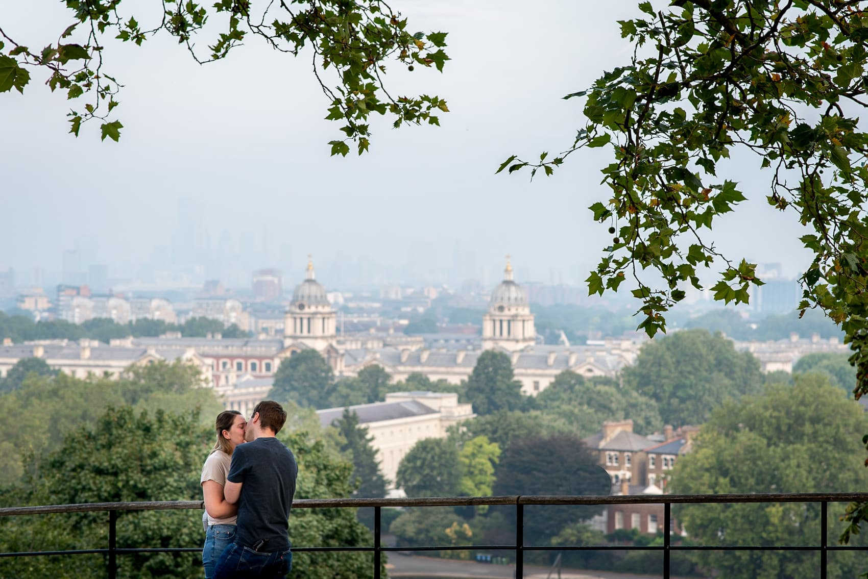Engaged couple kissing in Greenwich park, over looking london