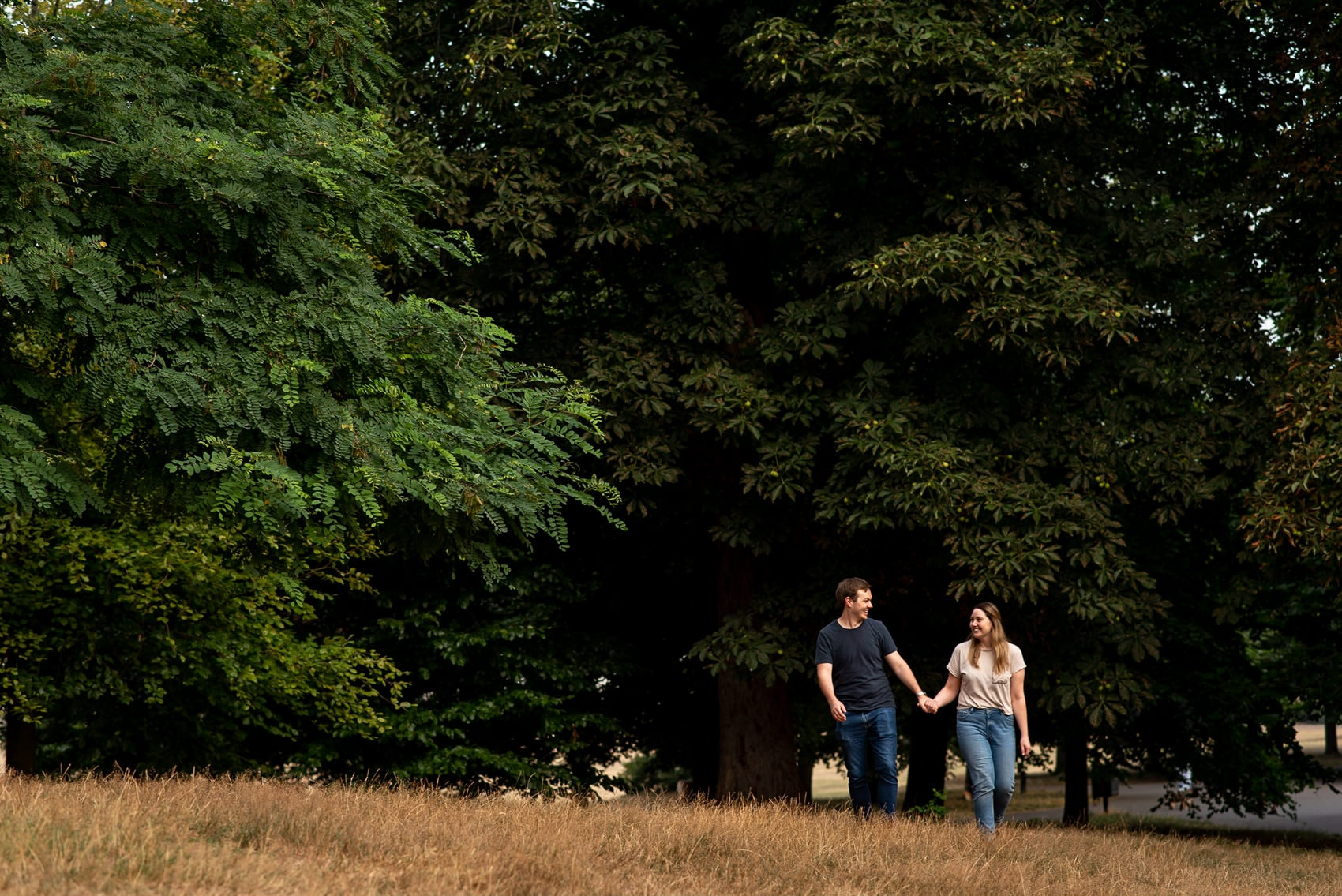couple waking in the trees during their greenwich park engagement shoot