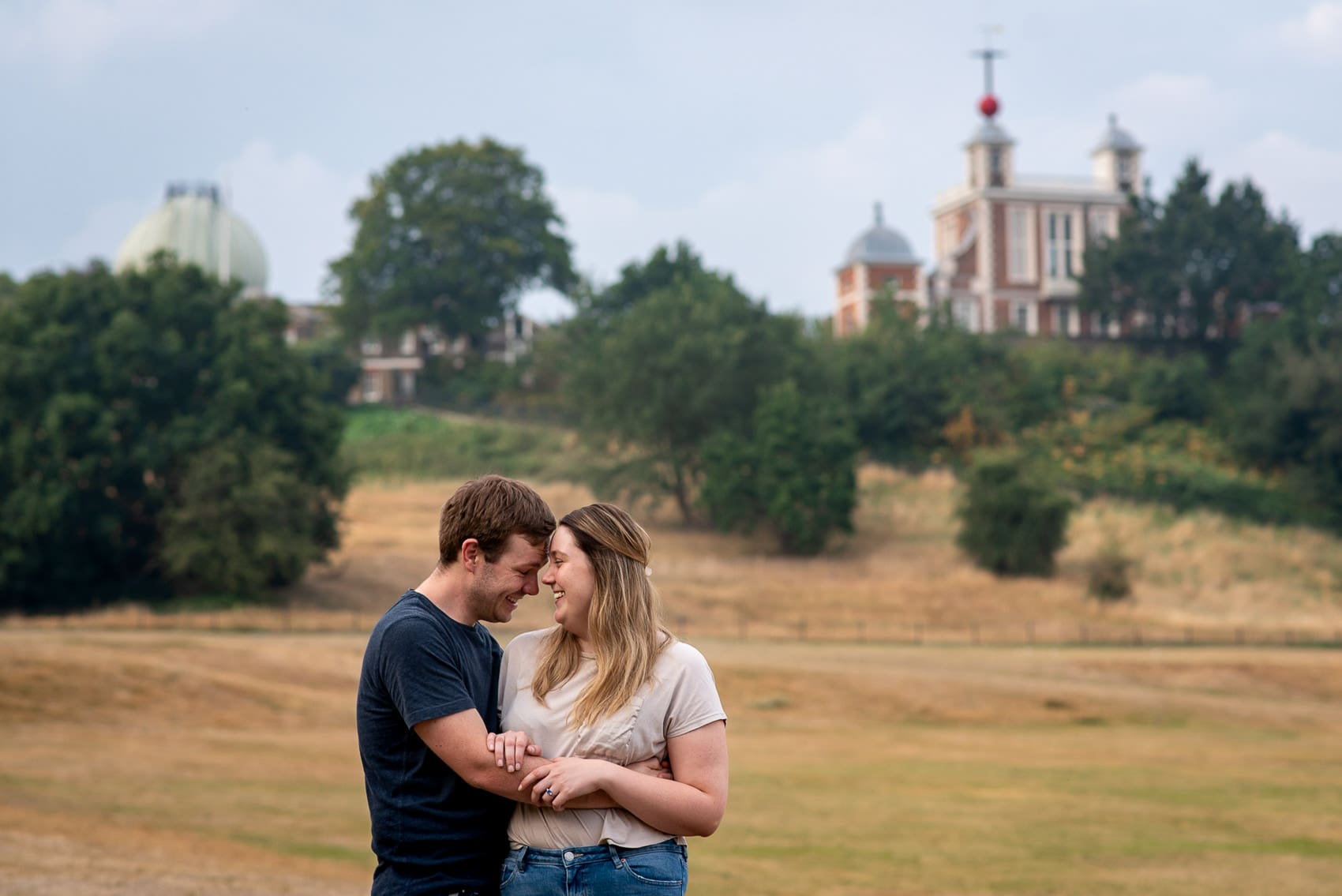 couple laughing in front of the Royal Observatory on their Greenwich park engagement shoot london