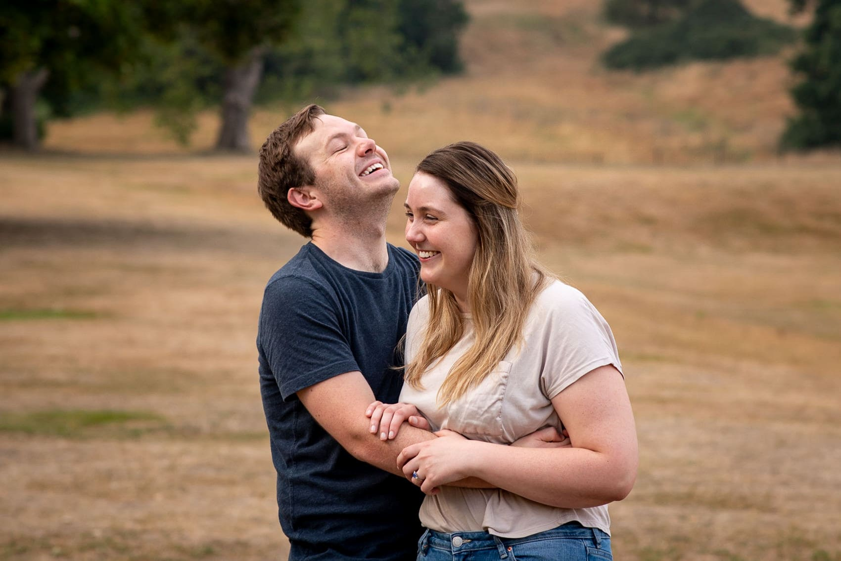 boyfriend and girlfriend laughing and hugging in greenwich park