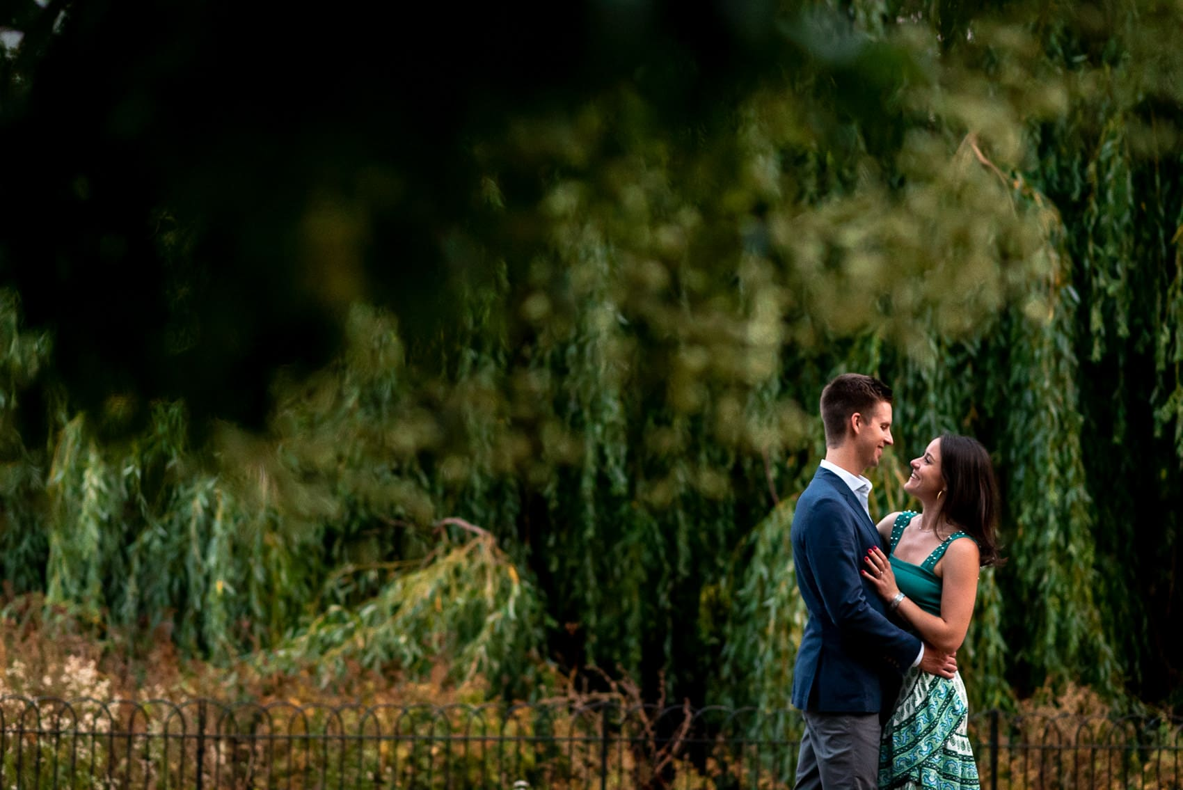 Photo of couple in St James Park amongst the trees on their engagement shoot