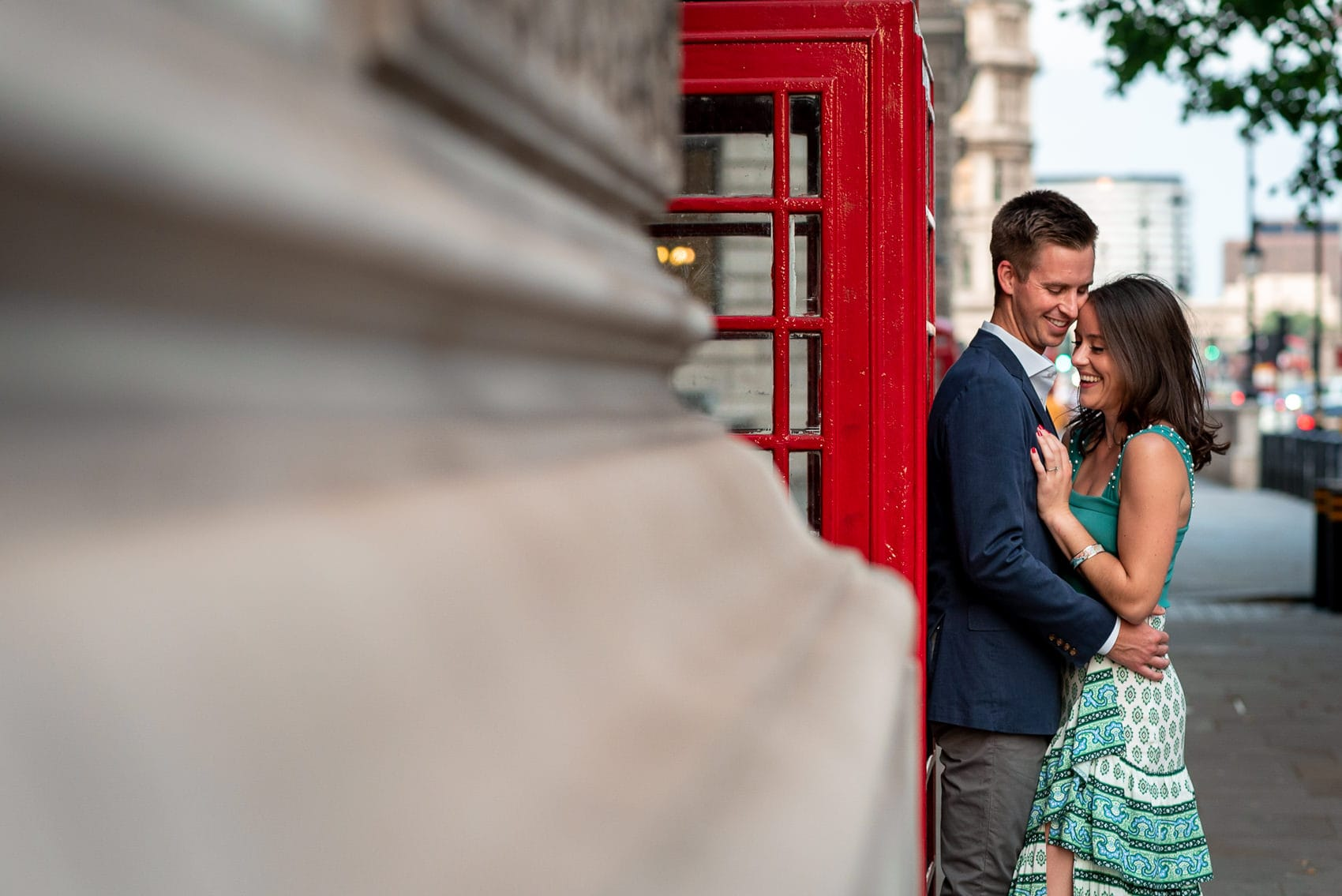 Couple laughing outside a Red Phone box in Westminster