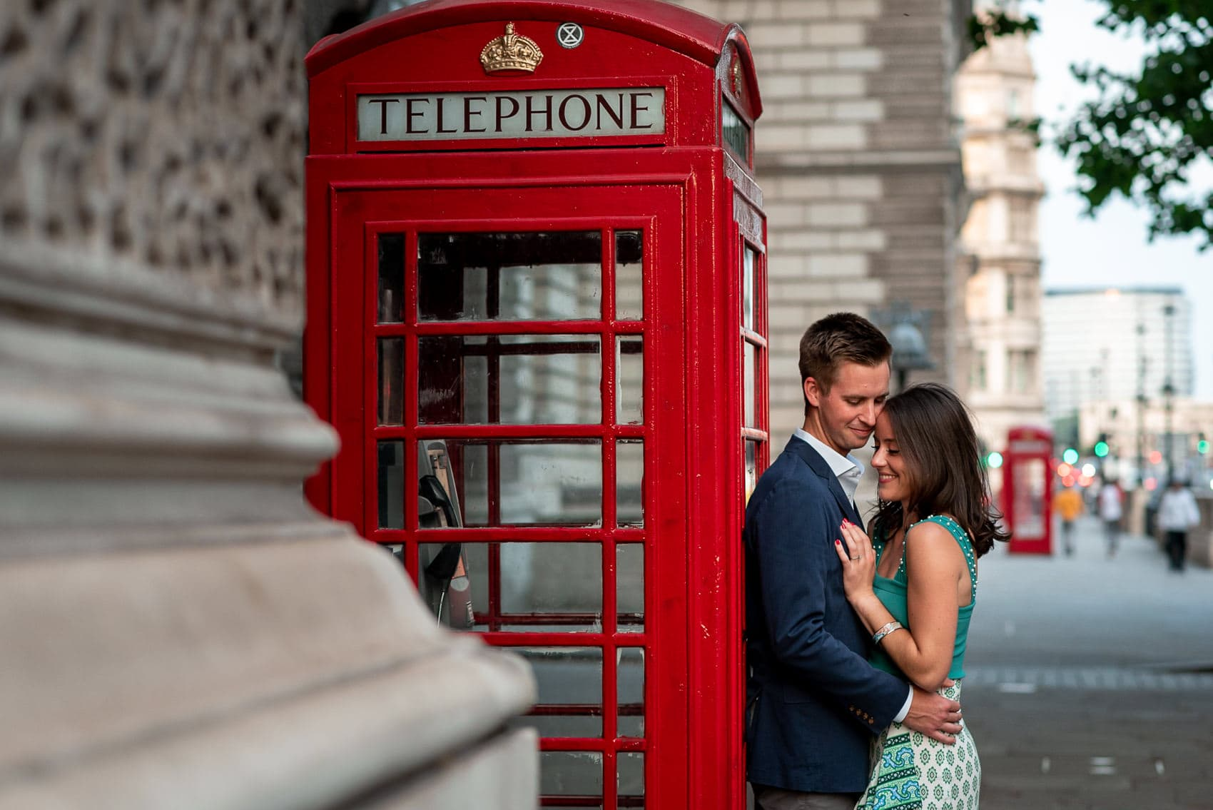 A couple posing next to a London Red Telephone Box in Westminster