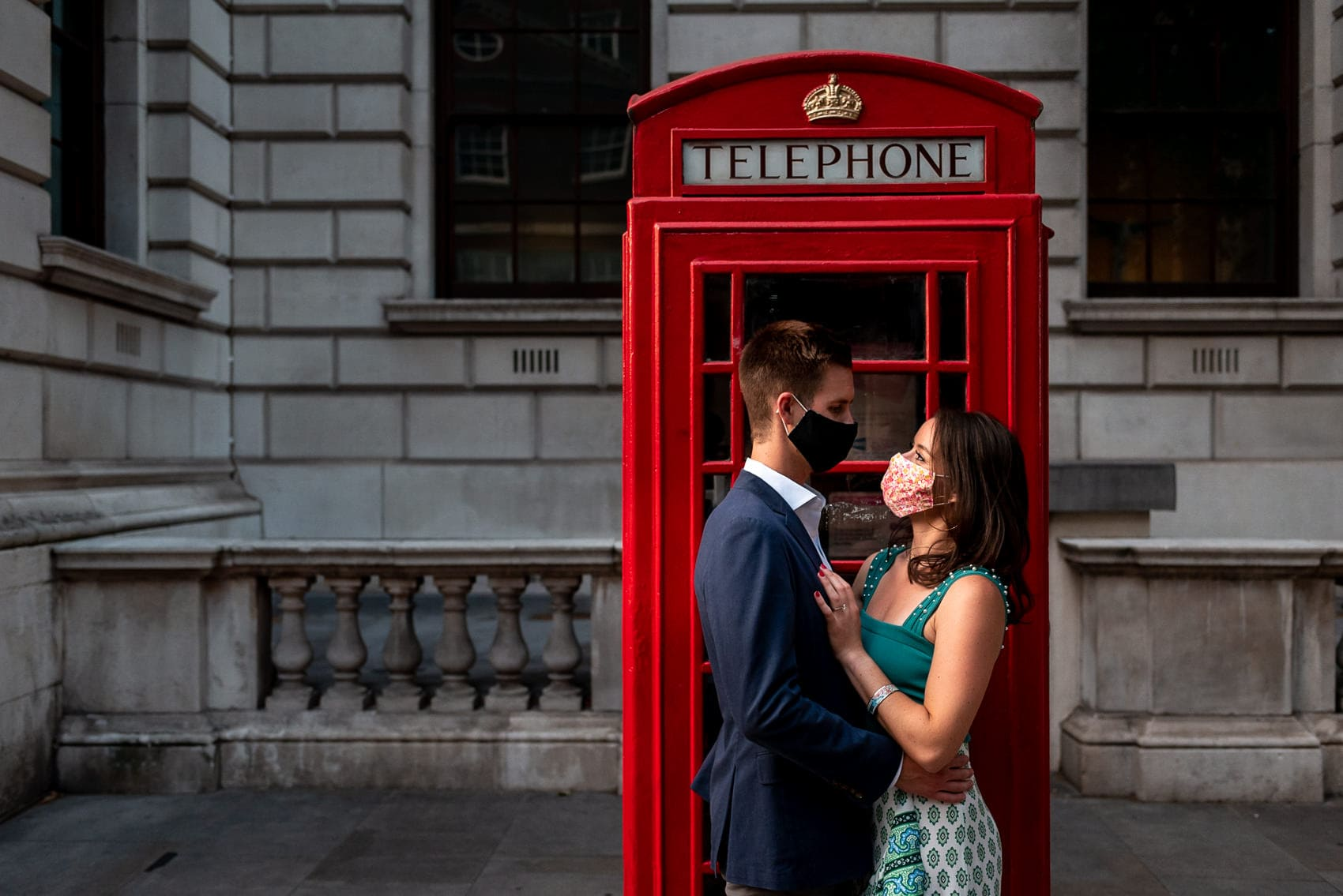 A couple with masks on in front of a red Telephone on their London engagement shoot during the Covid19 pandemic
