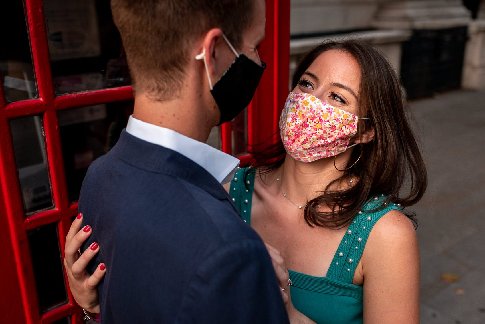 A couple smiling in masks during their engagement shoot