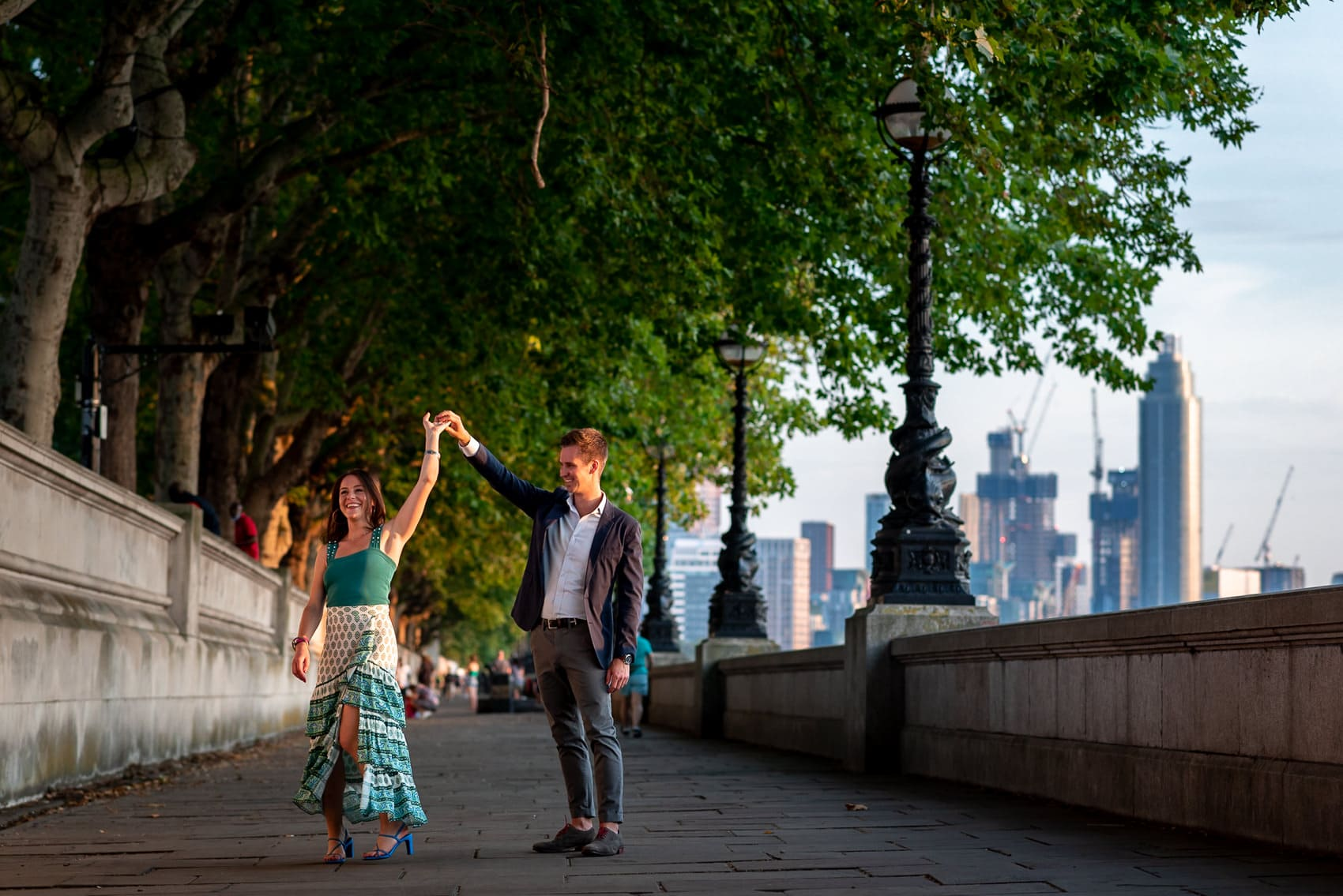 Couple dancing at sunset along the Thames walkway opposite Big Ben in London