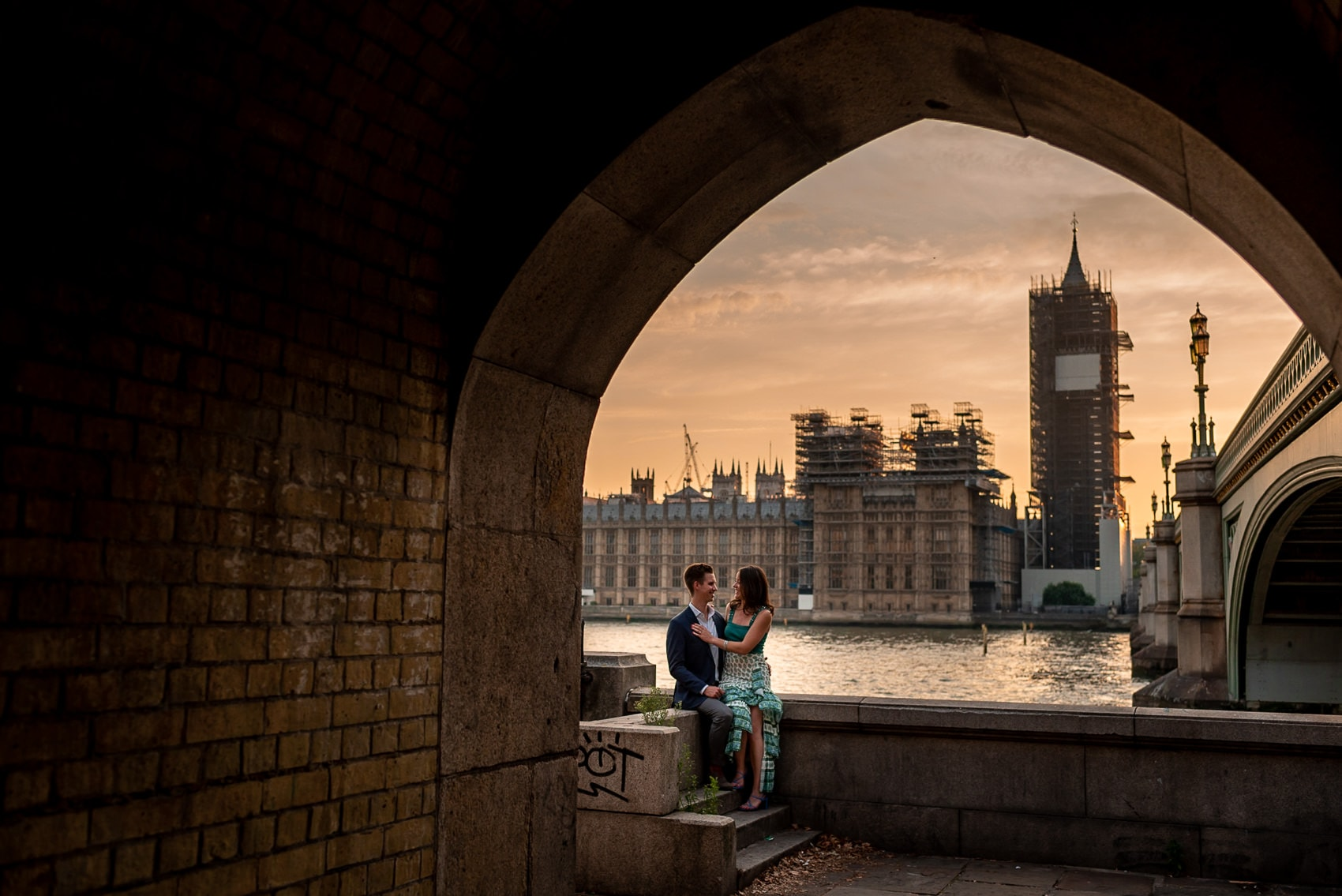Couple sitting next to the thames in front of Big Ben with scaffolding at sunset