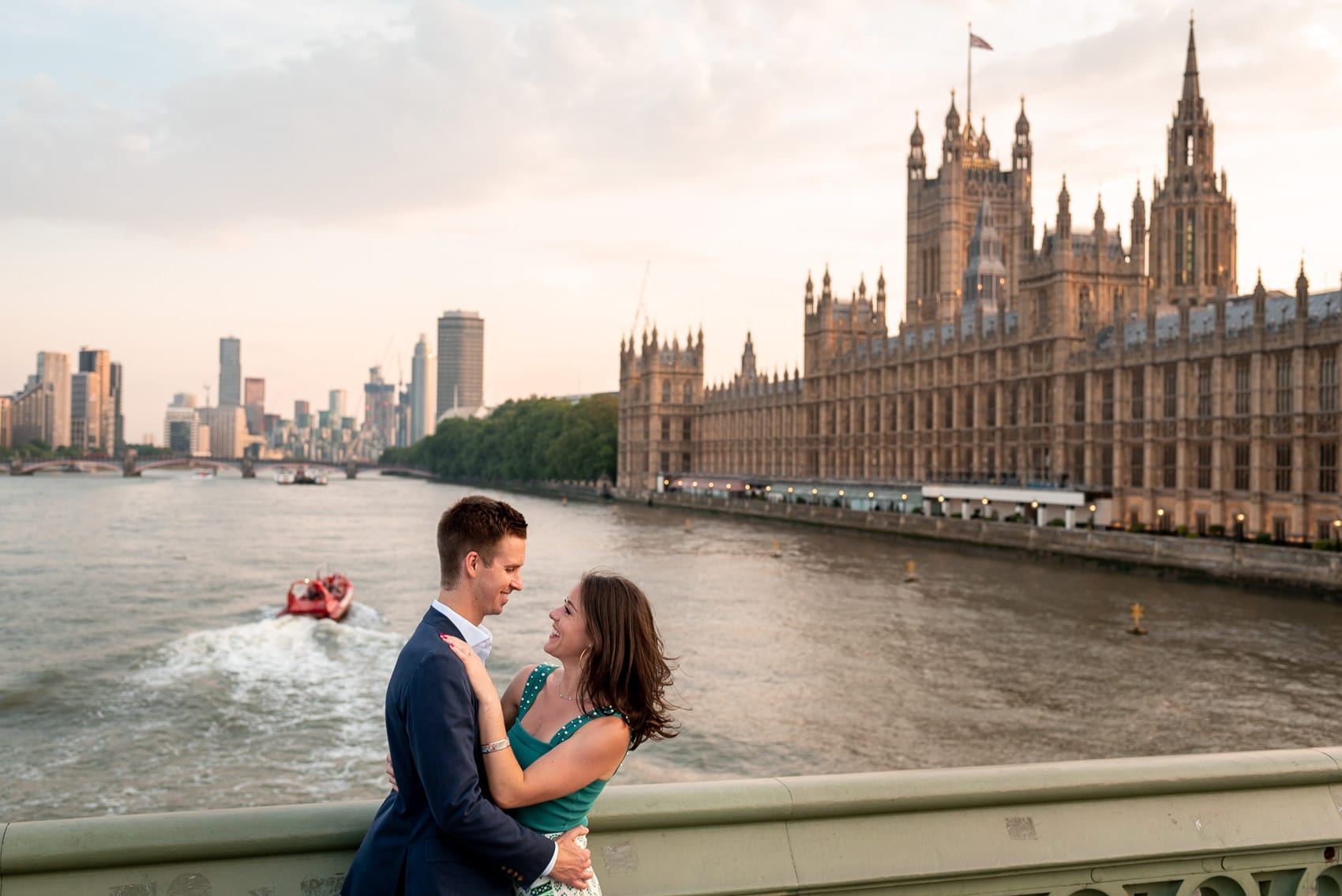 couple outside of the Houses of Parliament and the Thames at sunset during their London Engagement shoot in Westminster