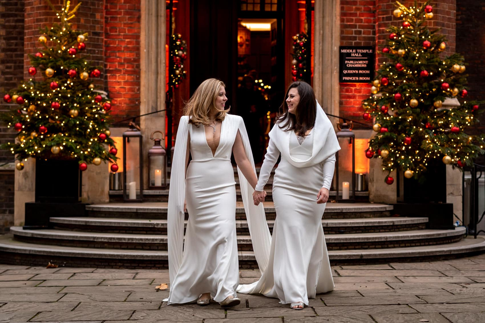two brides with Christmas Trees outside Middle Temple for their same sex winter wedding photos