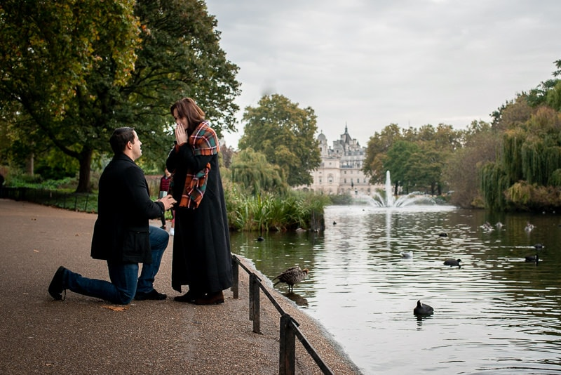 Photo of man proposing to his girlfriend next to the lake in St James Park, London