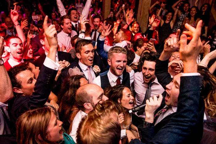 Photo of groom partying with friends at his London wedding