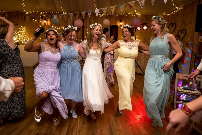 Photo of bride dancing with her bridesmaids at her wedding