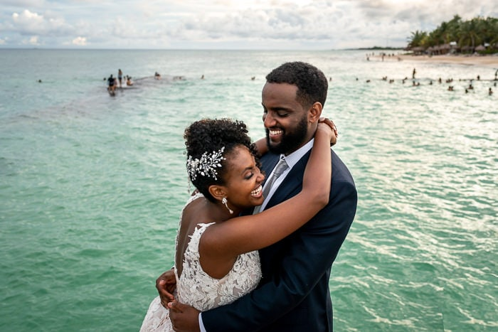 Photo of wedding bride and groom laughing by the sea
